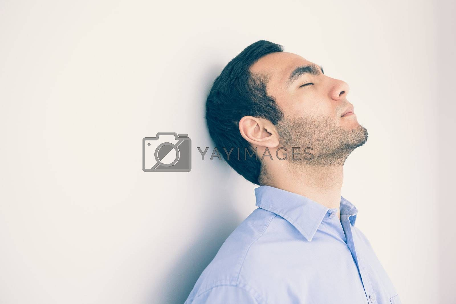Thoughtful man leaning against a wall by Wavebreakmedia