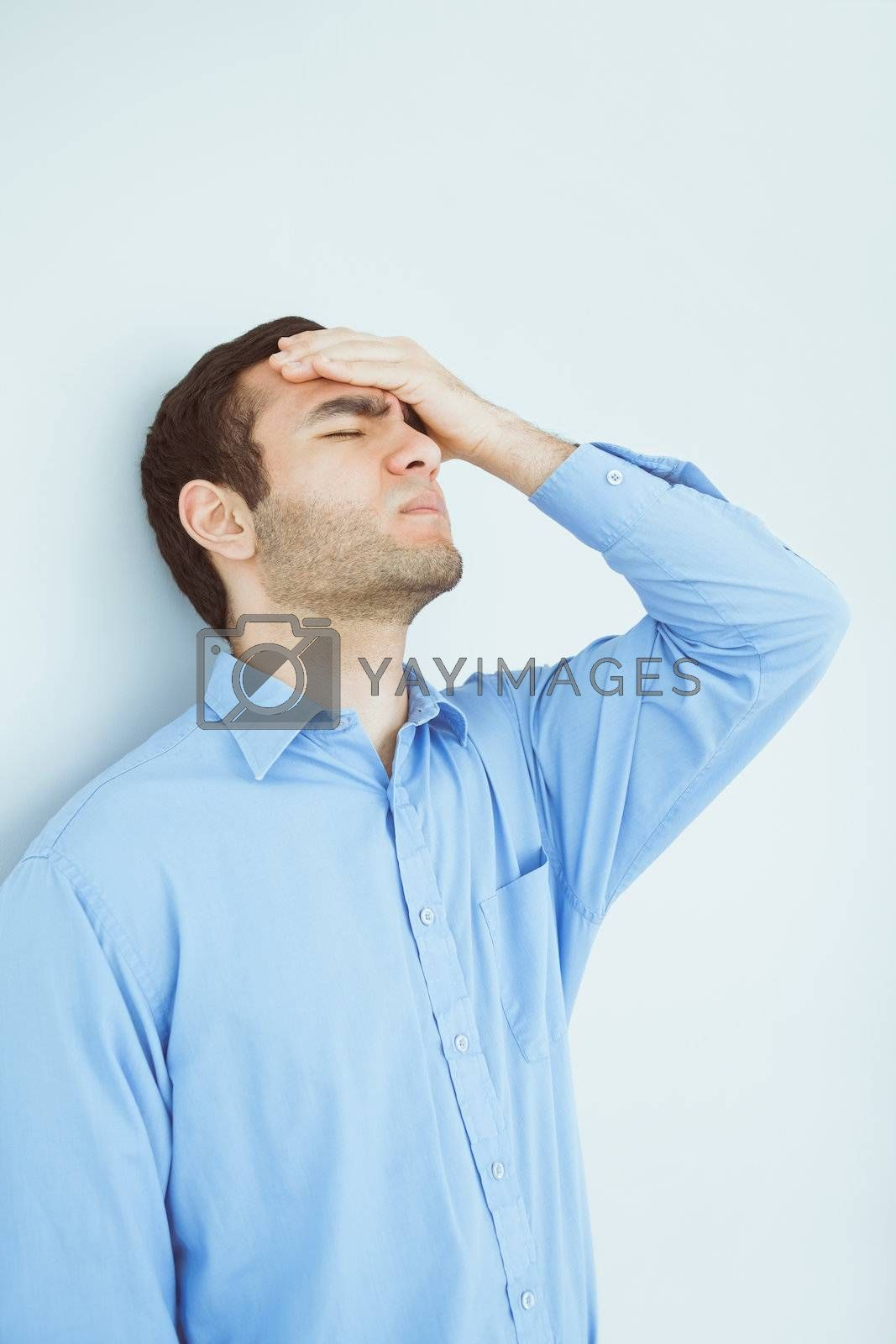 Upset man eyes closed and a hand on the forehead leaning against a wall by Wavebreakmedia