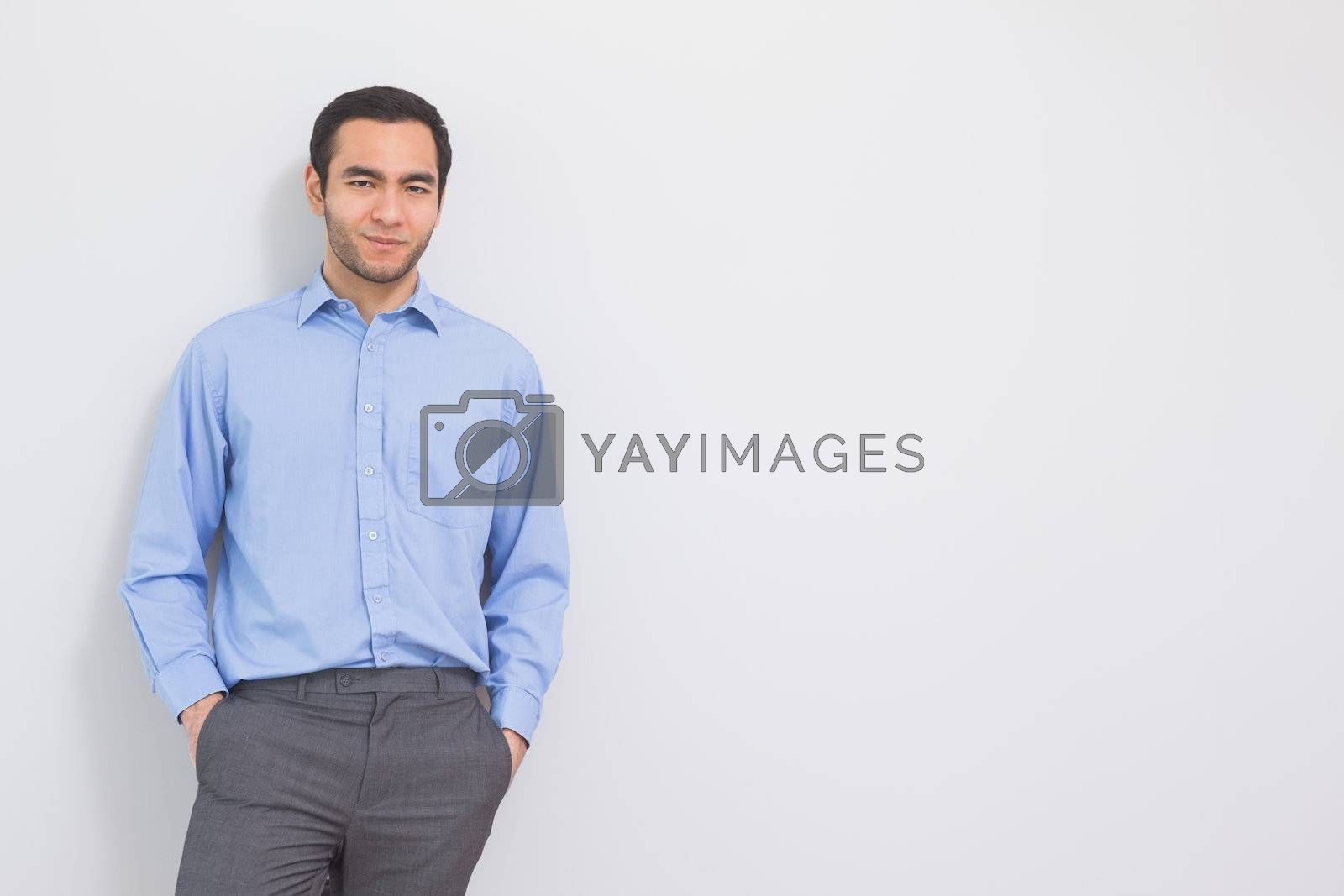Content man leaning against a wall hands in the pockets  by Wavebreakmedia