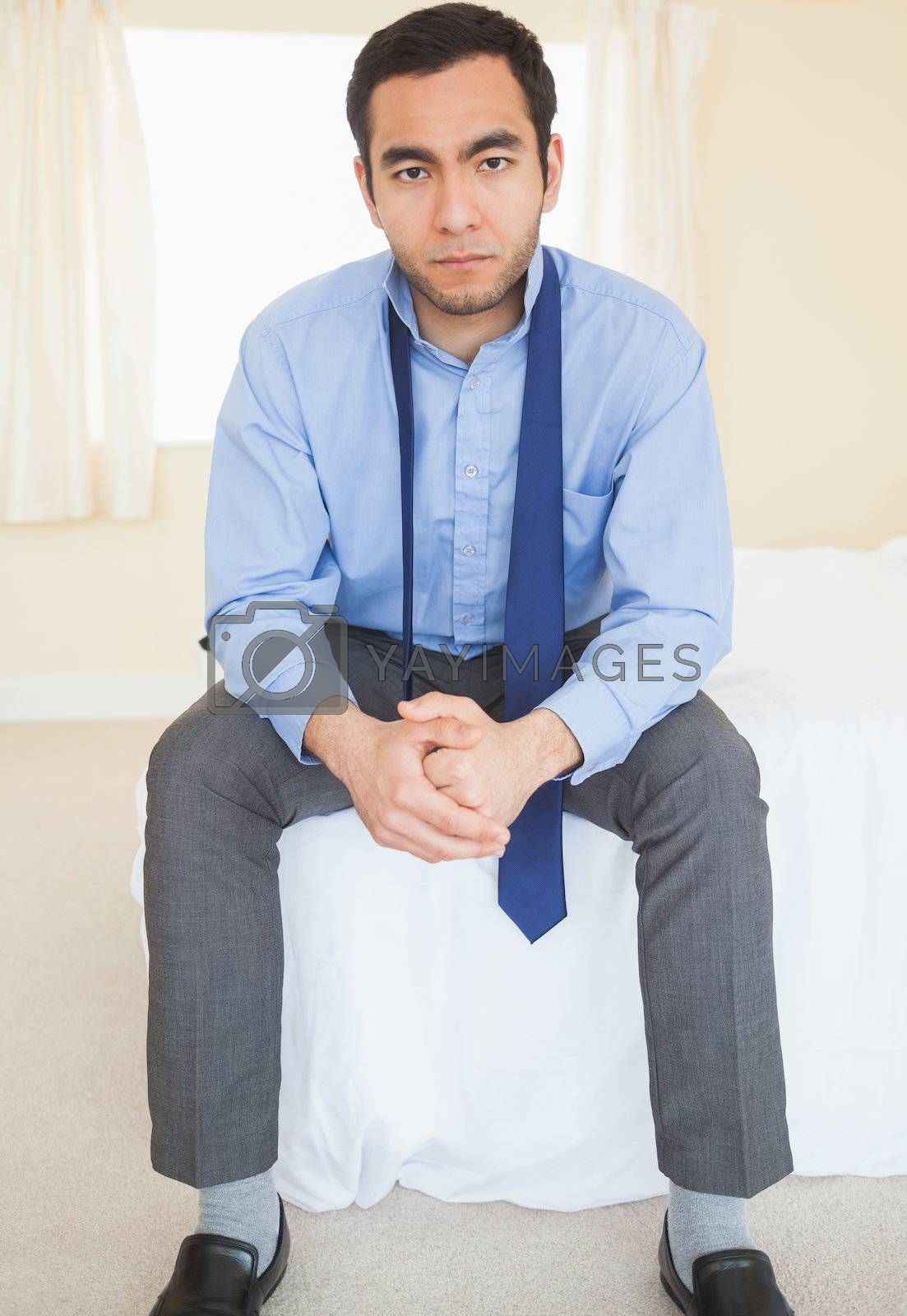 Unsmiling man sitting on his bed by Wavebreakmedia