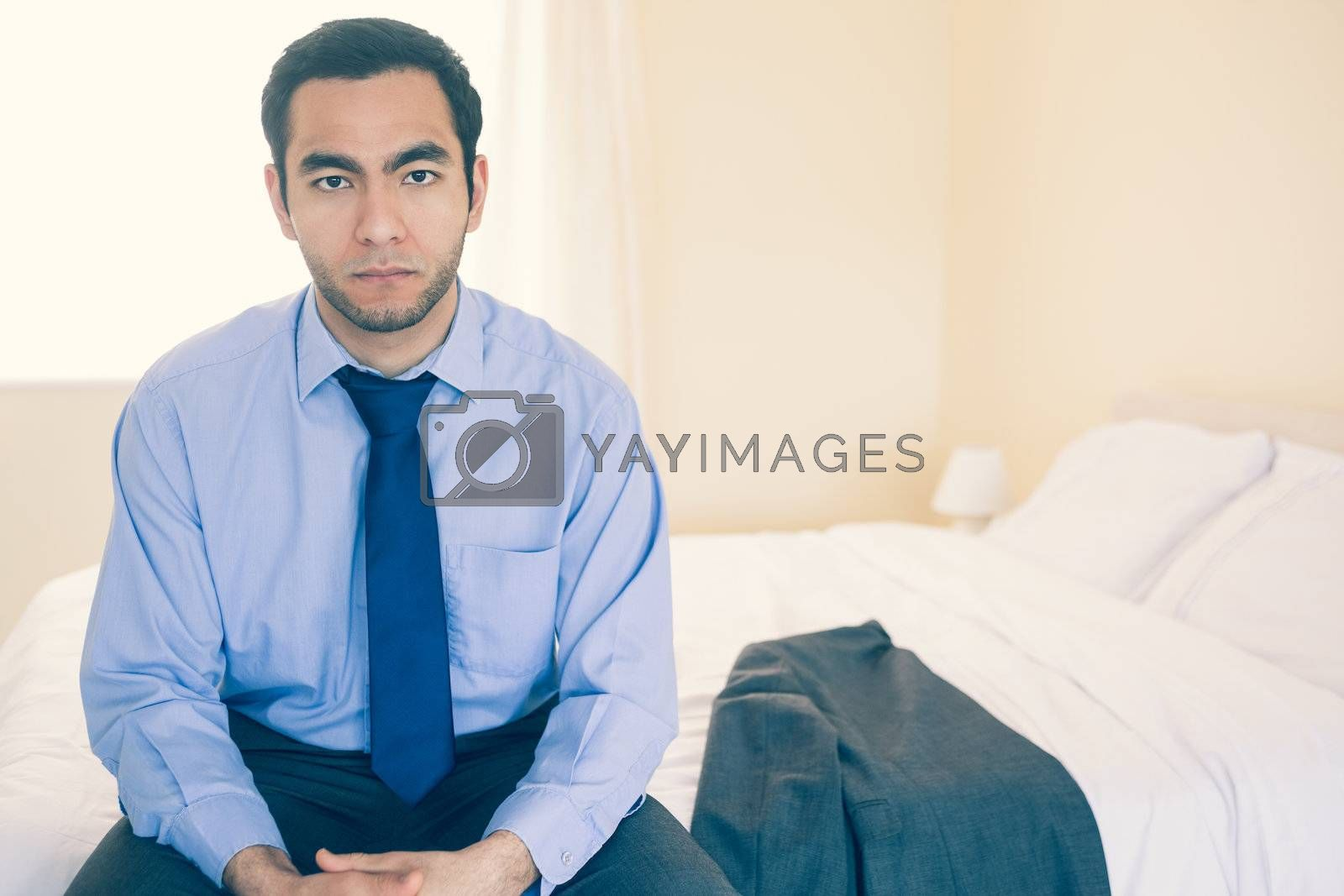 Frowning man looking at camera sitting on his bed by Wavebreakmedia