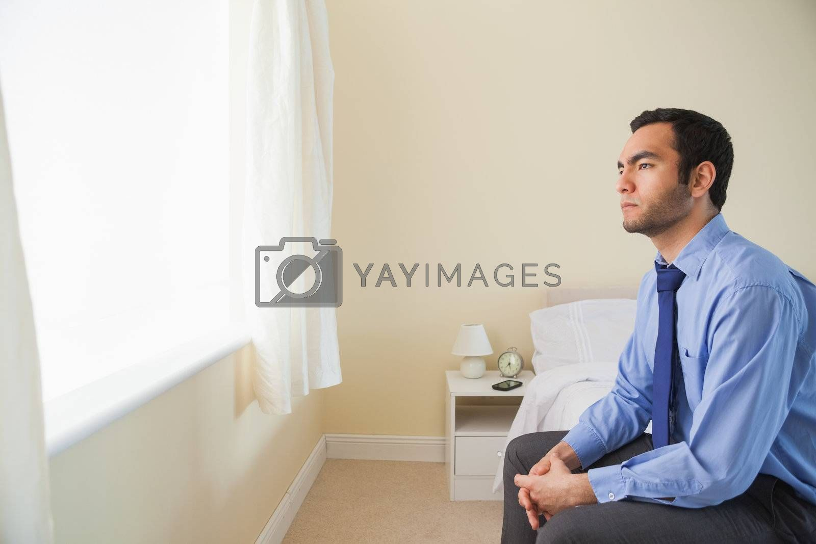 Unsmiling man looking out the window sitting on his bed by Wavebreakmedia