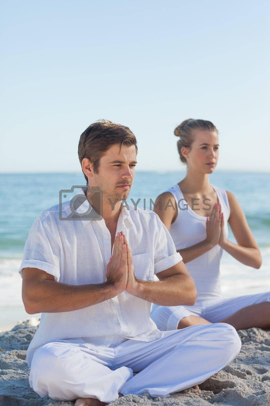Man and woman practicing yoga by Wavebreakmedia