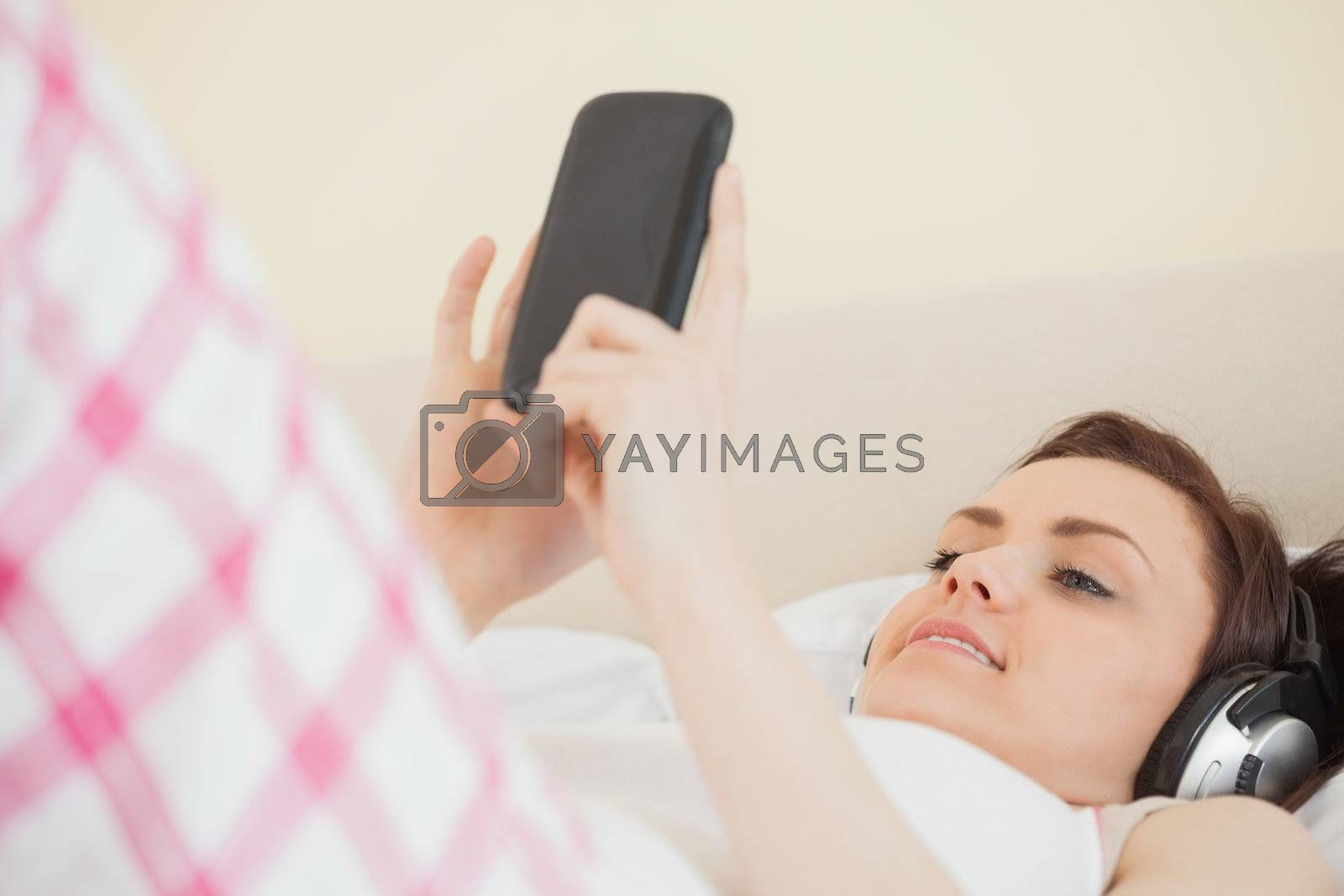 Smiling girl listening to music and using a mobile phone lying on a bed by Wavebreakmedia