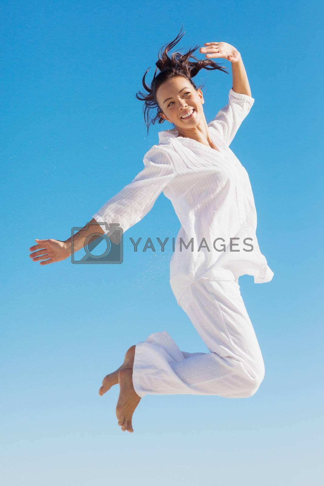Brunette woman jumping by Wavebreakmedia