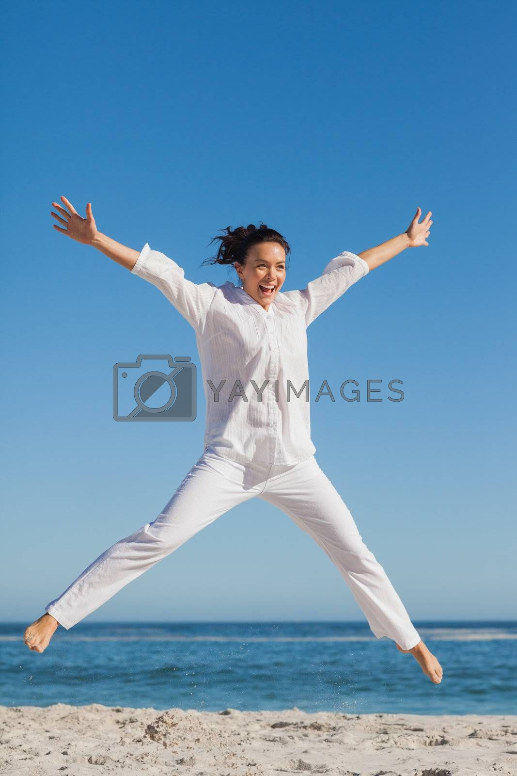 Happy woman jumping on the beach by Wavebreakmedia