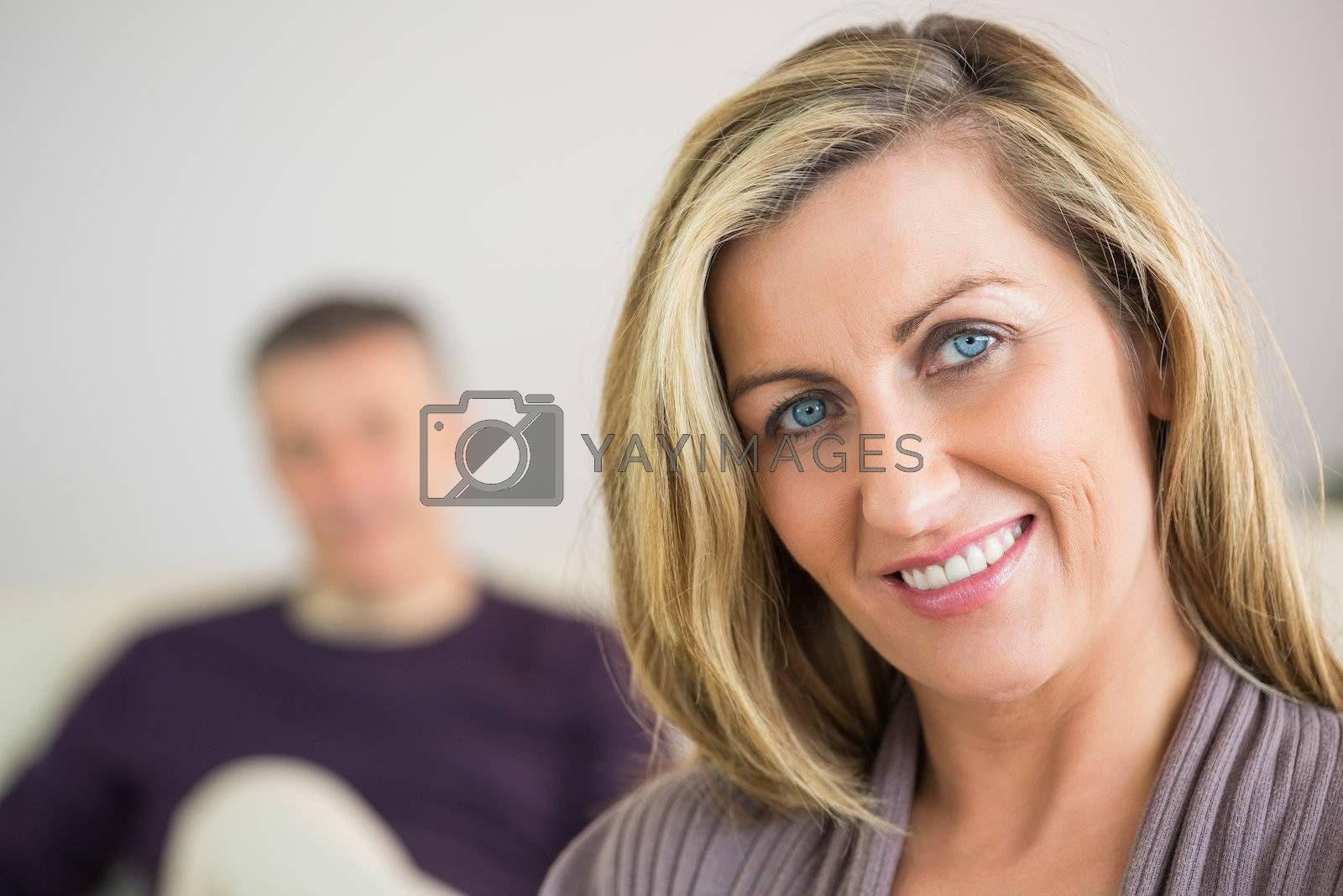 Smiling woman with her husband in the background by Wavebreakmedia