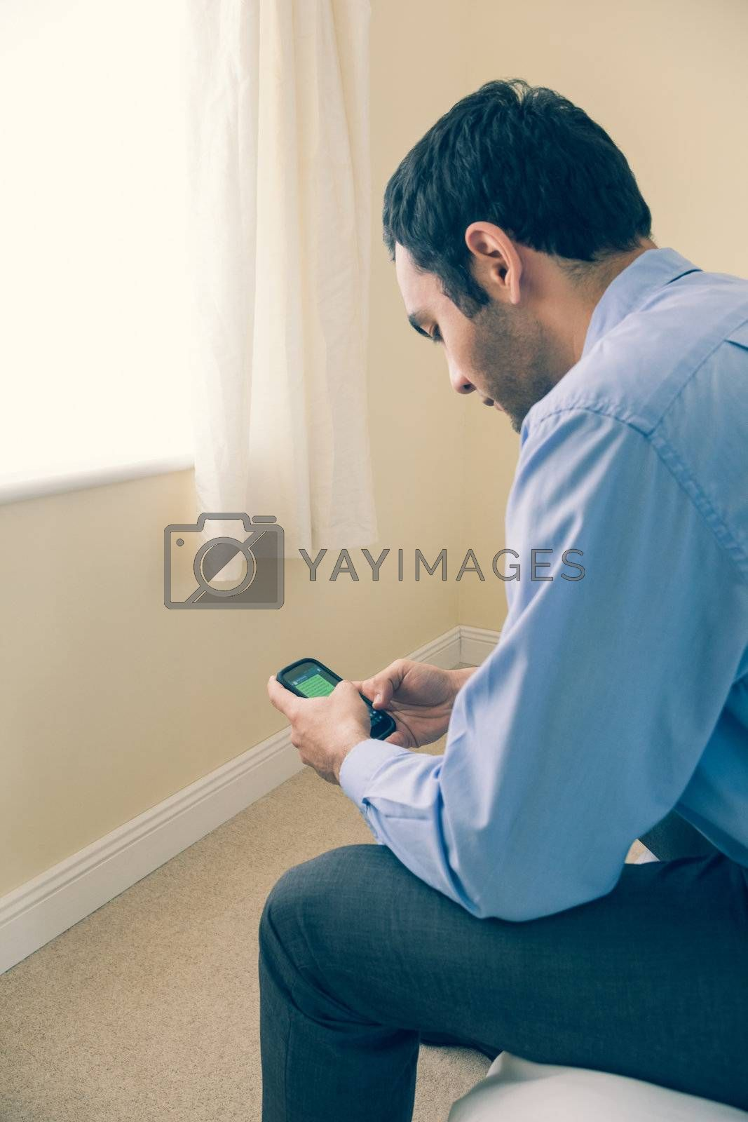 Man using a mobile phone sitting on a bed by Wavebreakmedia