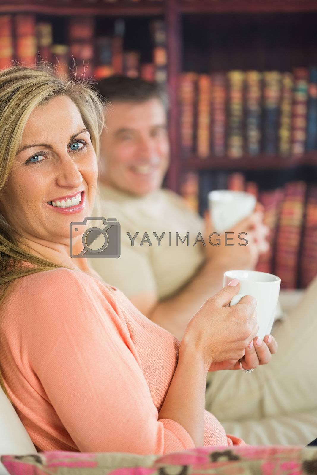 Happy couple drinking coffee sitting on a sofa by Wavebreakmedia