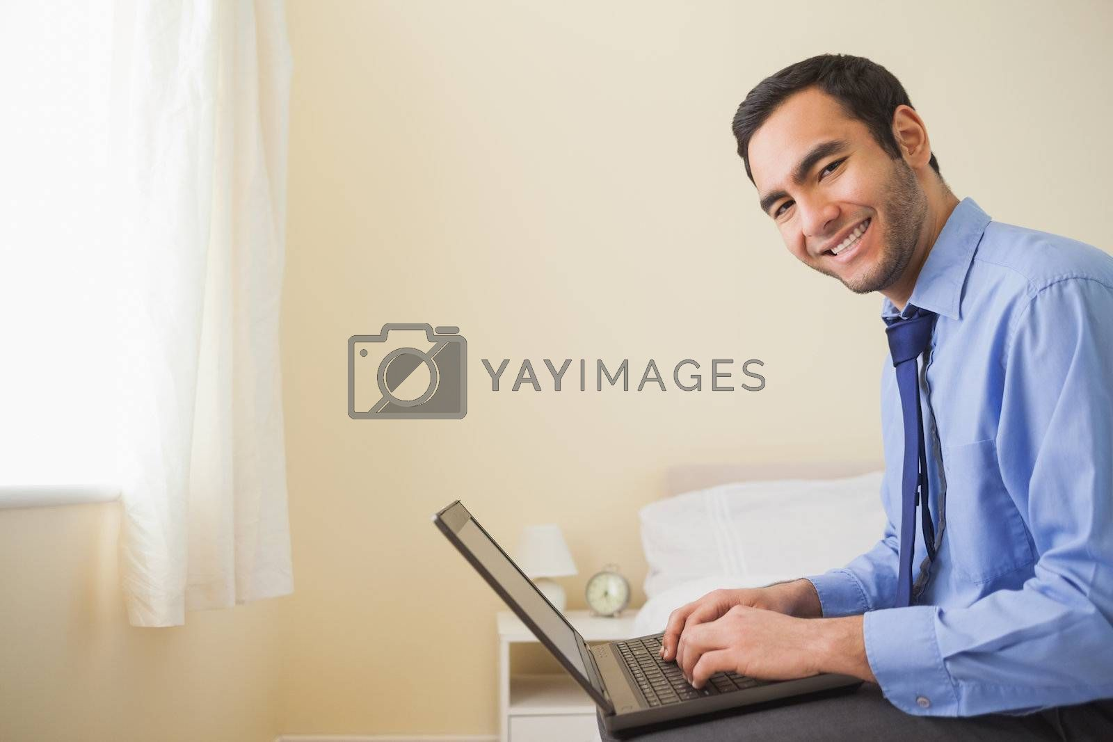 Smiling man using a laptop sitting on bed by Wavebreakmedia