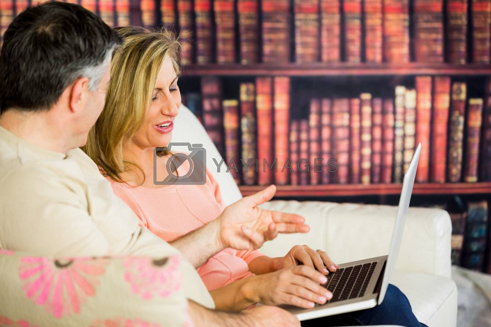 Happy couple sitting on a sofa in a reading room watching a laptop by Wavebreakmedia