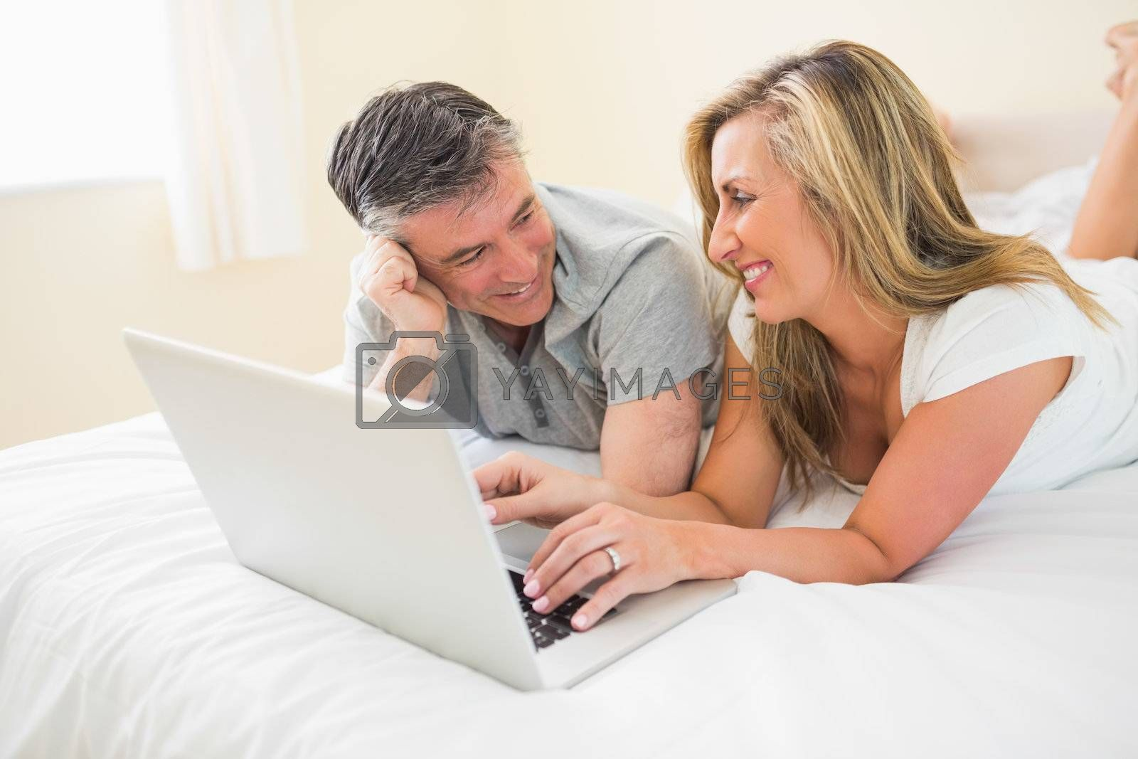 Laughing couple lying on bed using a laptop by Wavebreakmedia