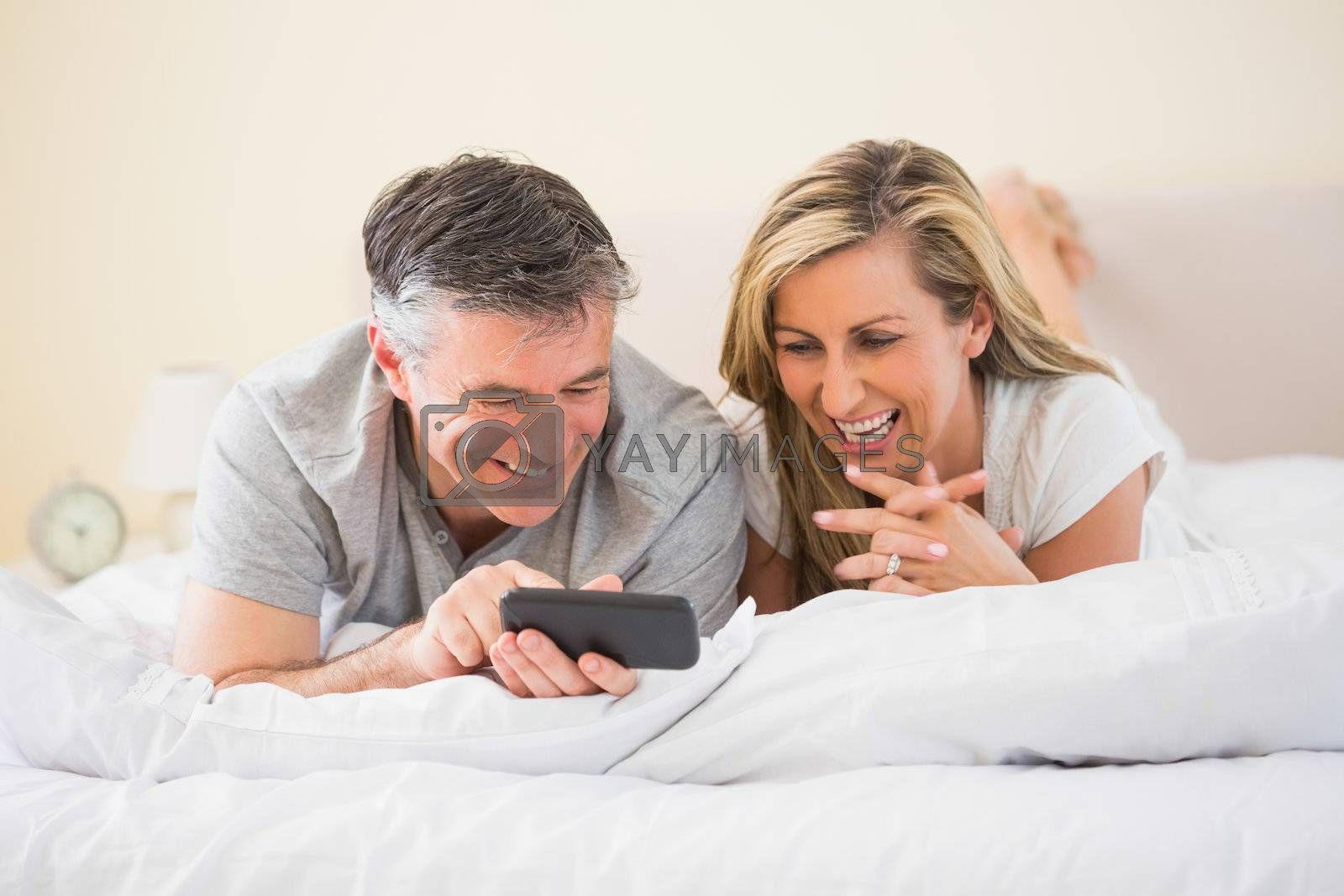 Happy couple lying on bed and watching a mobile phone by Wavebreakmedia