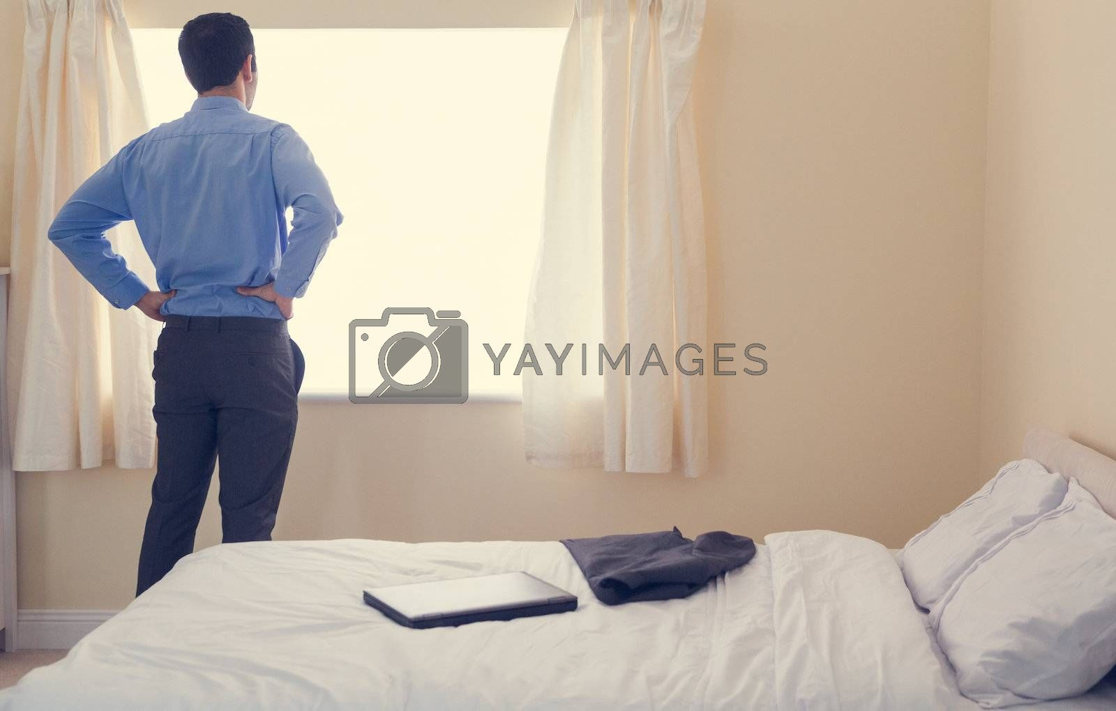 Rear view of a man standing in front of a window and looking out it by Wavebreakmedia