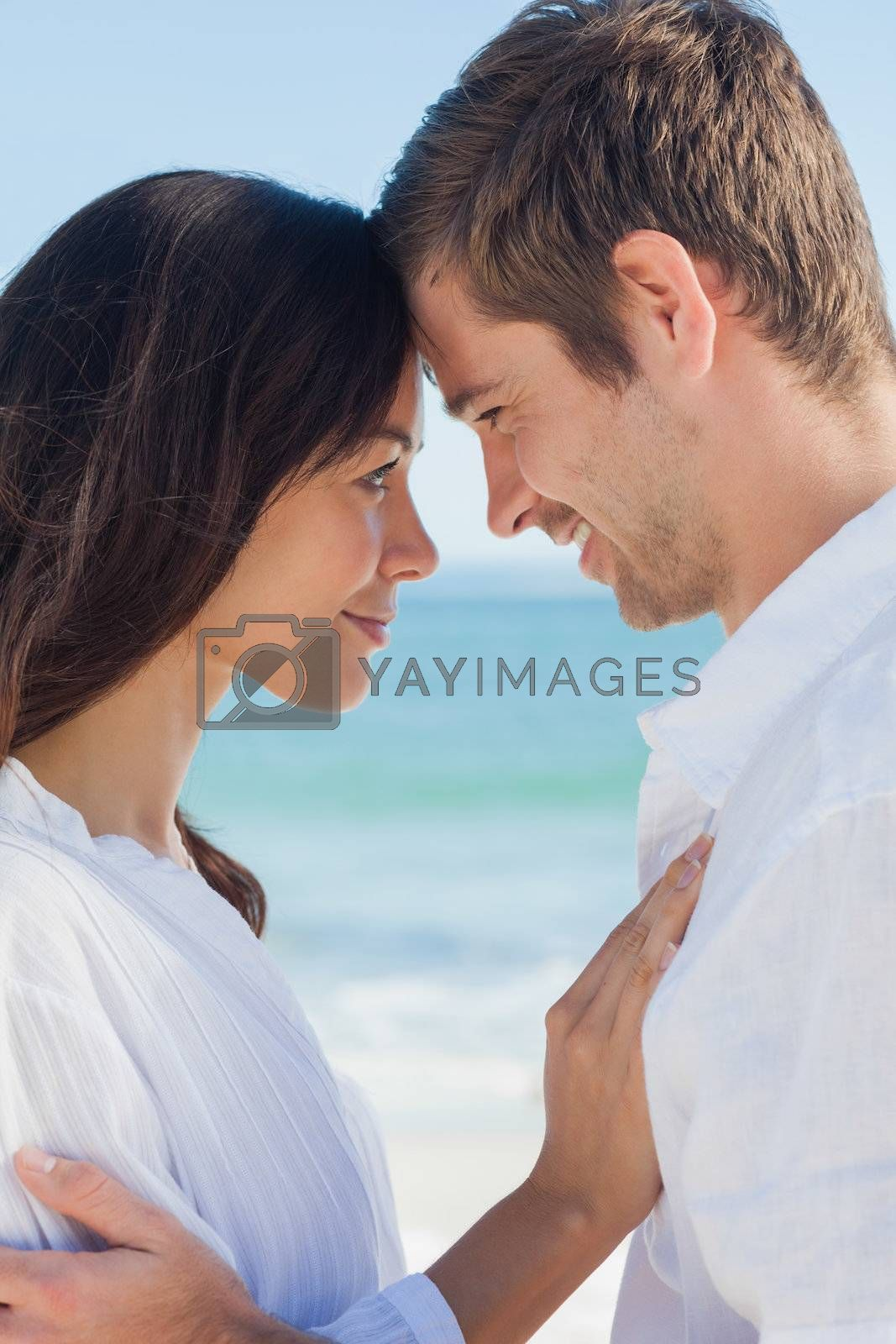 Romantic couple relaxing on the beach  by Wavebreakmedia