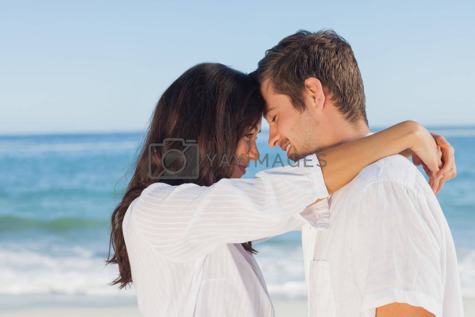 Couple embracing each other on the beach by Wavebreakmedia