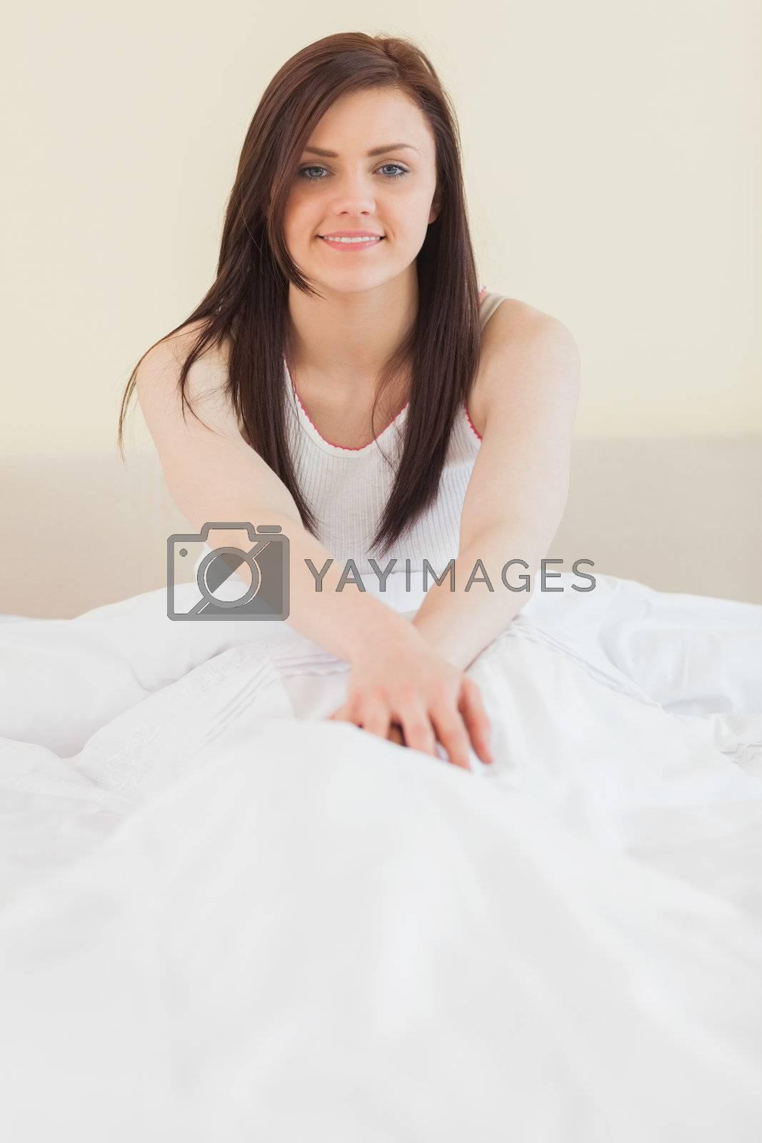 Awakened girl sitting in her bed looking  by Wavebreakmedia