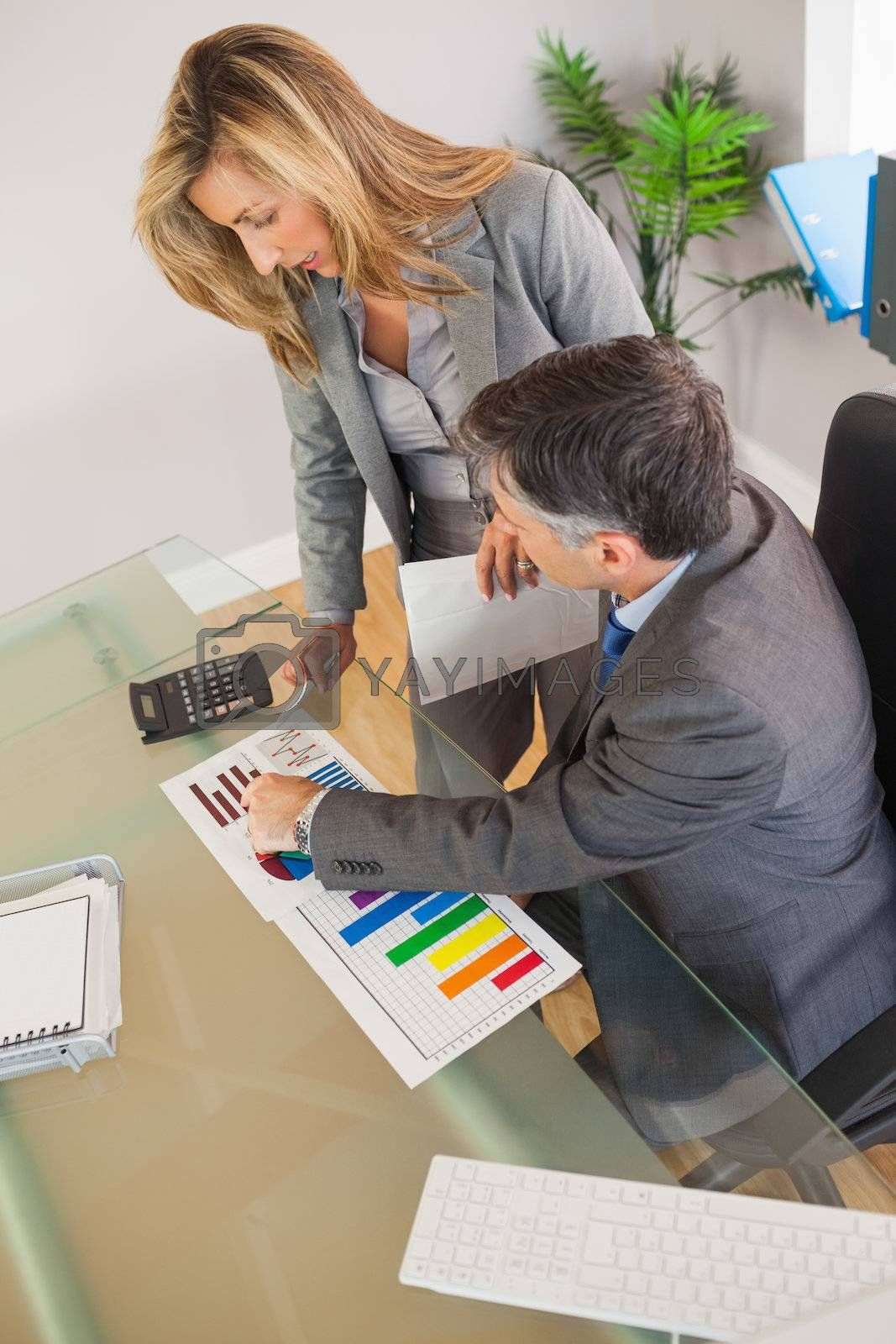 Two business people looking at documents in an office by Wavebreakmedia