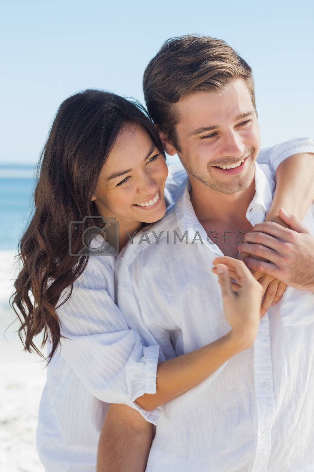 Smiling couple embracing each other on the beach by Wavebreakmedia