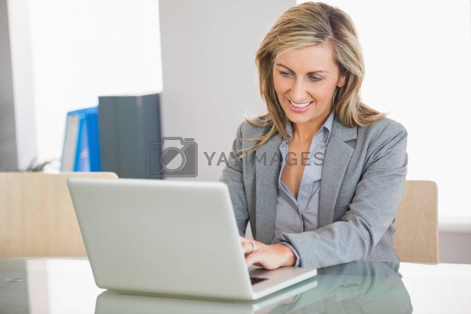 Businesswoman using a laptop in an office by Wavebreakmedia