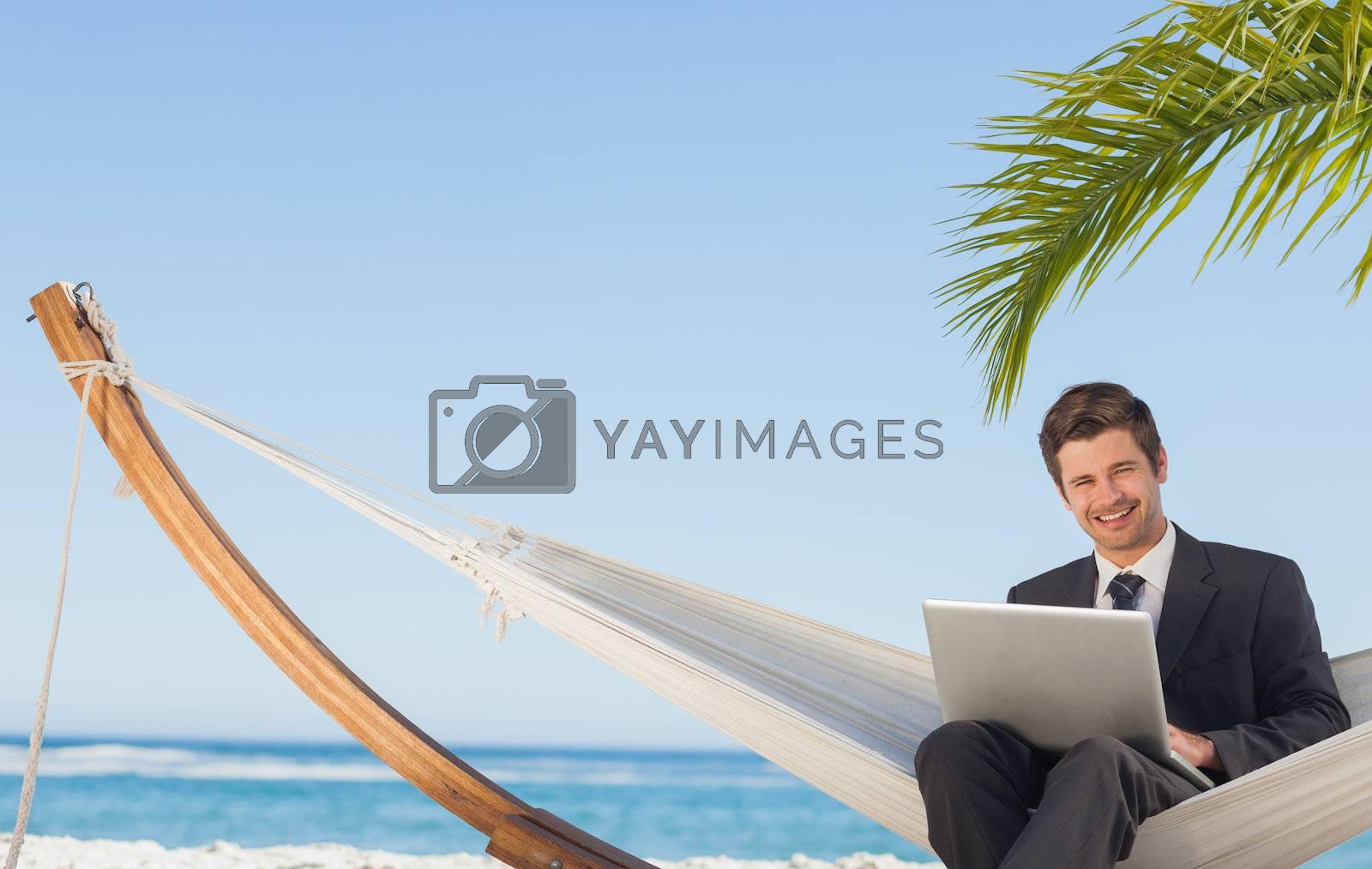 Businessman sitting in hammock using laptop looking at camera by Wavebreakmedia