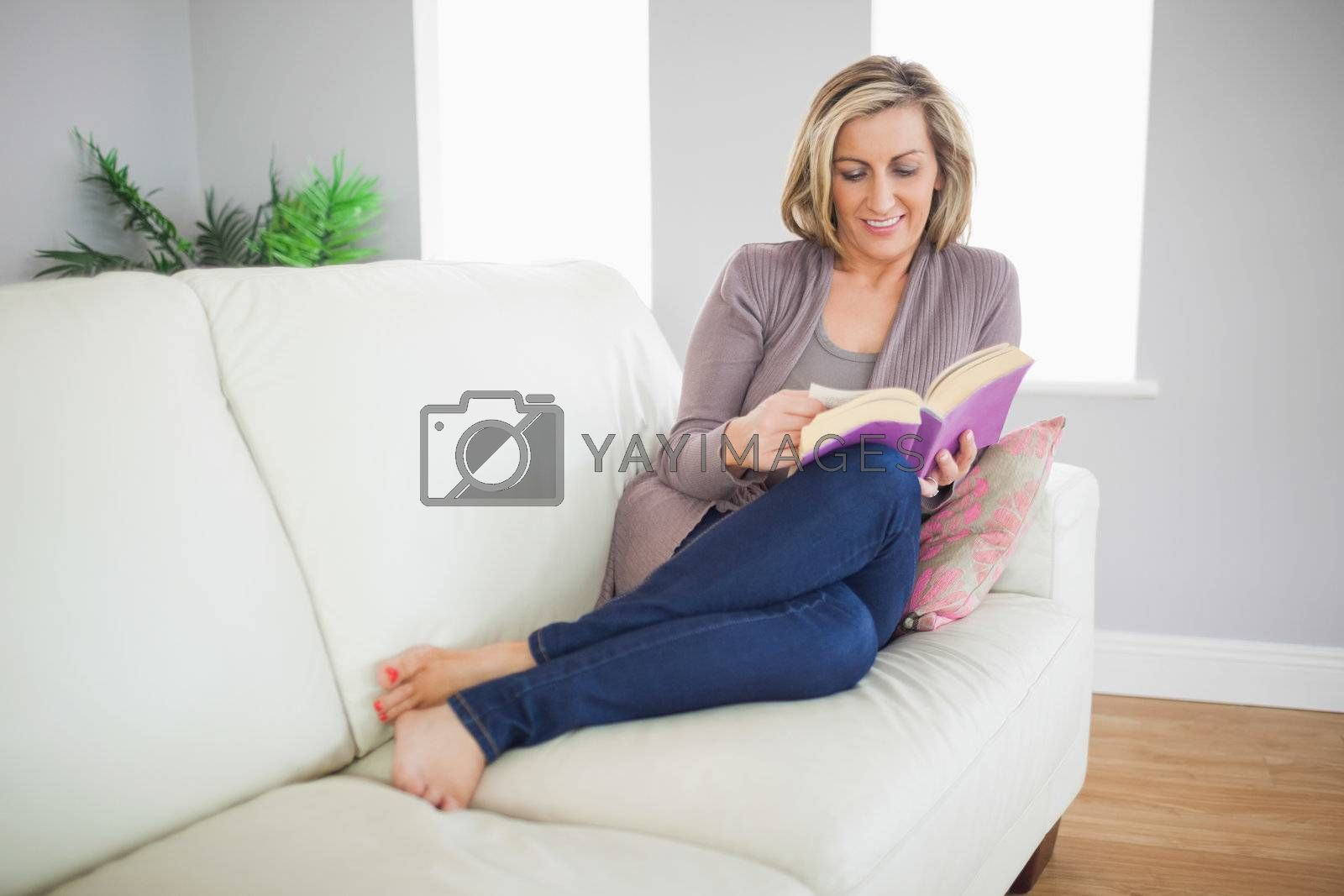 Smiling woman lying on sofa reading a book by Wavebreakmedia