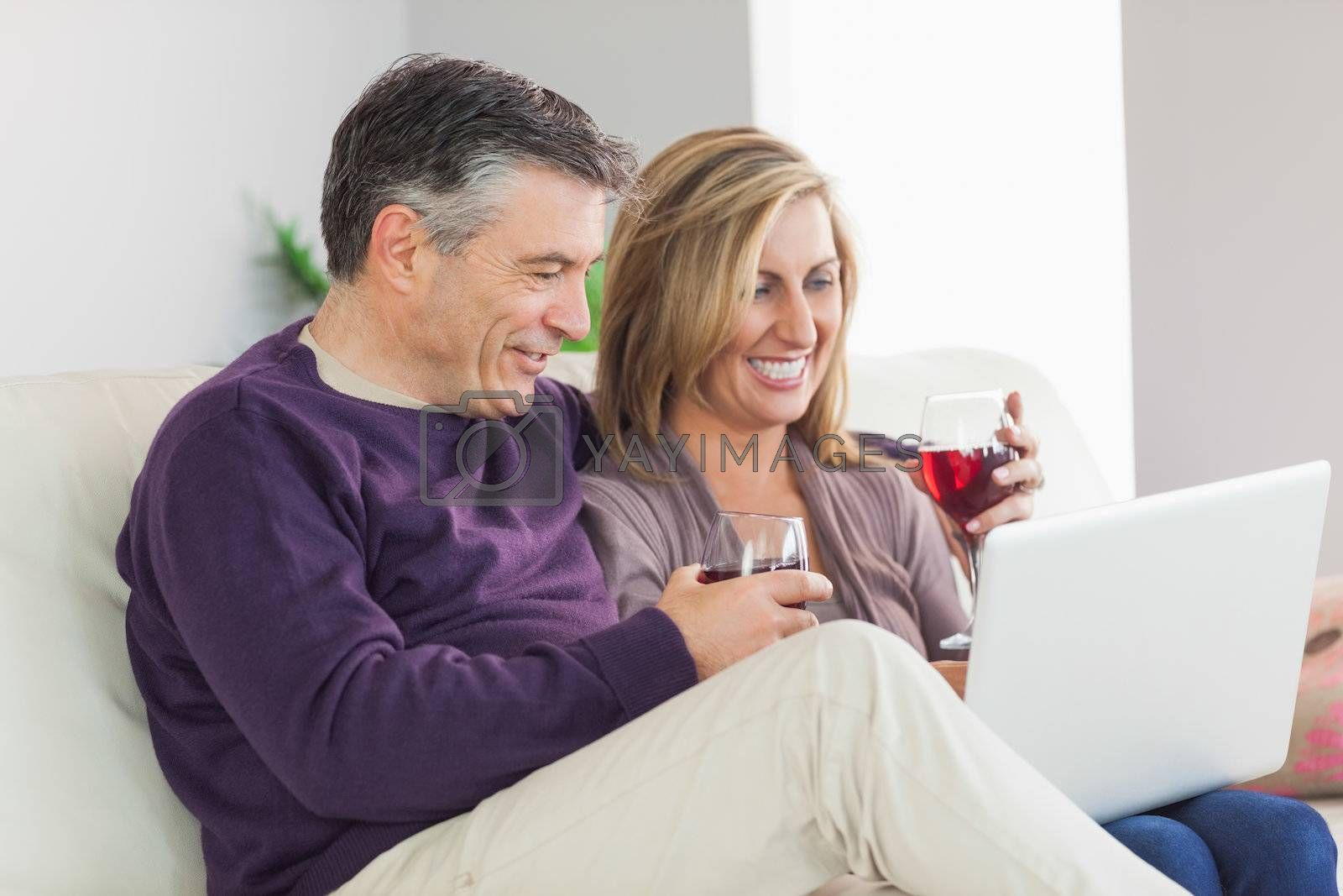 Happy couple watching their laptop and drinking wine by Wavebreakmedia