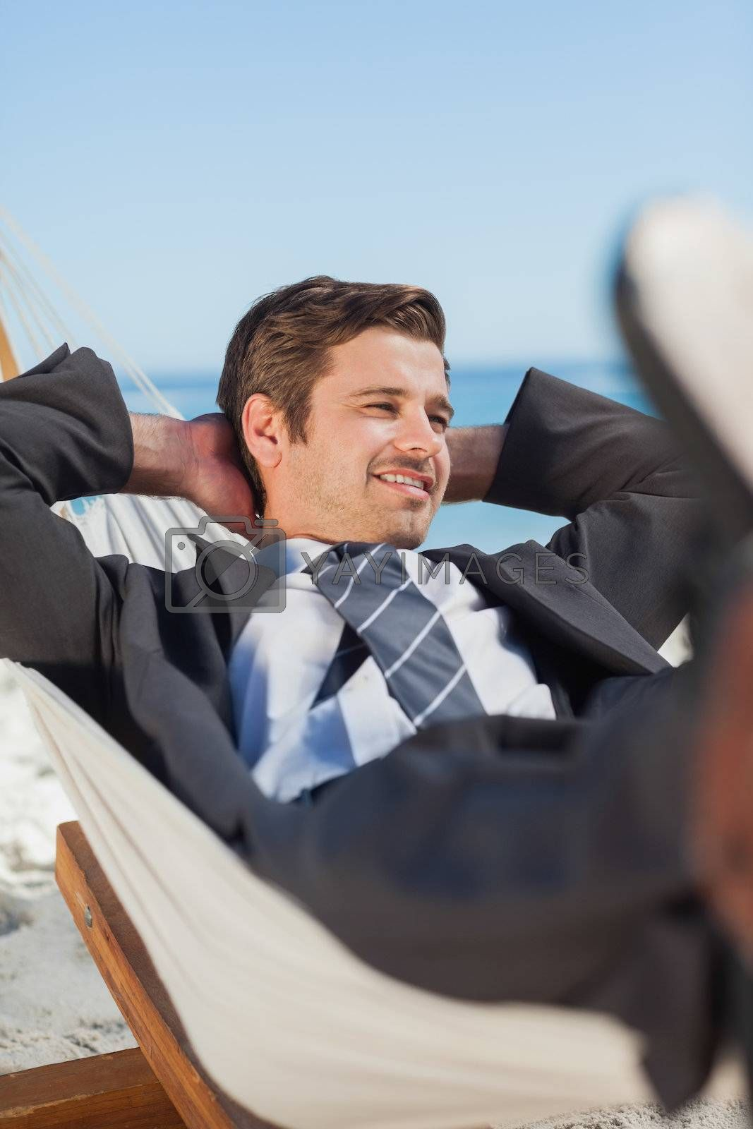 Happy businessman lying in hammock by Wavebreakmedia