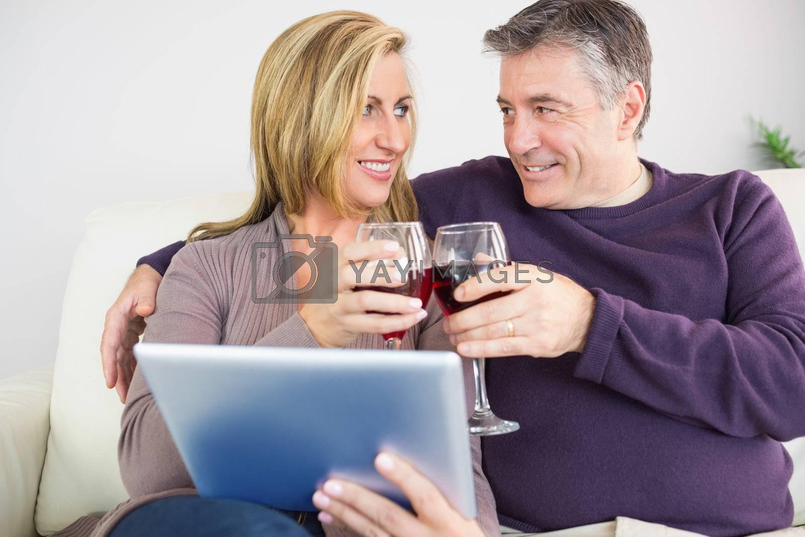 Happy couple toasting with wine sitting on sofa by Wavebreakmedia