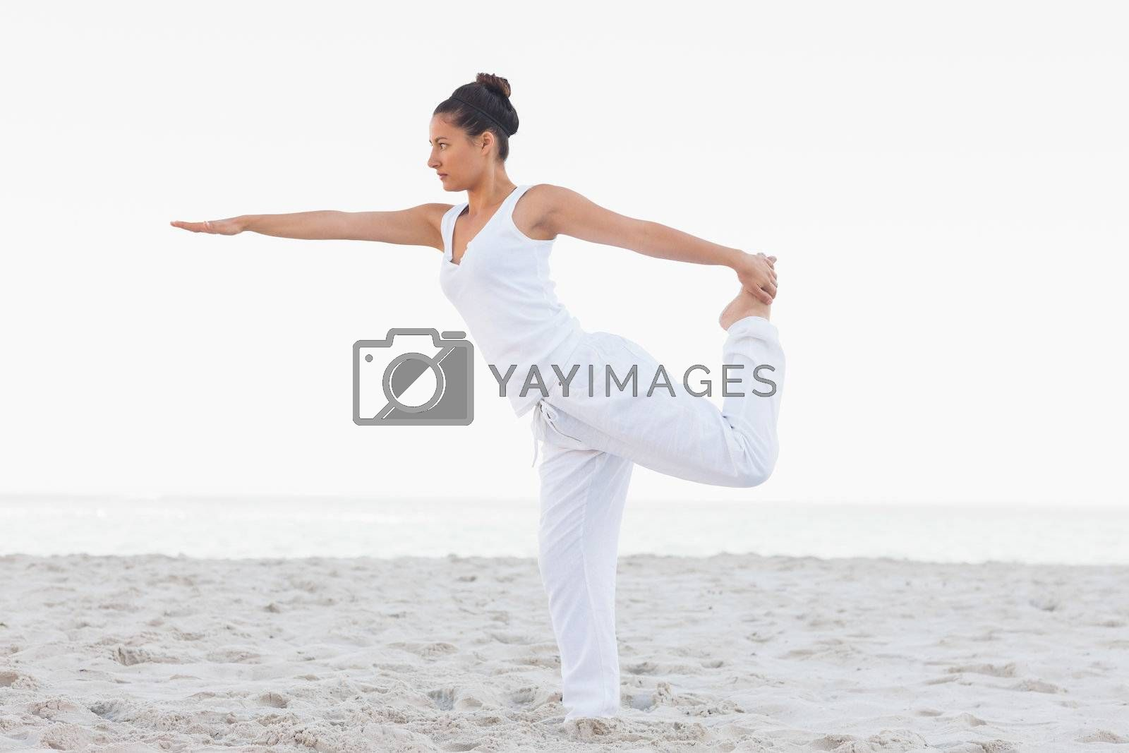 Brunette woman wearing all white stretching in yoga pose by Wavebreakmedia