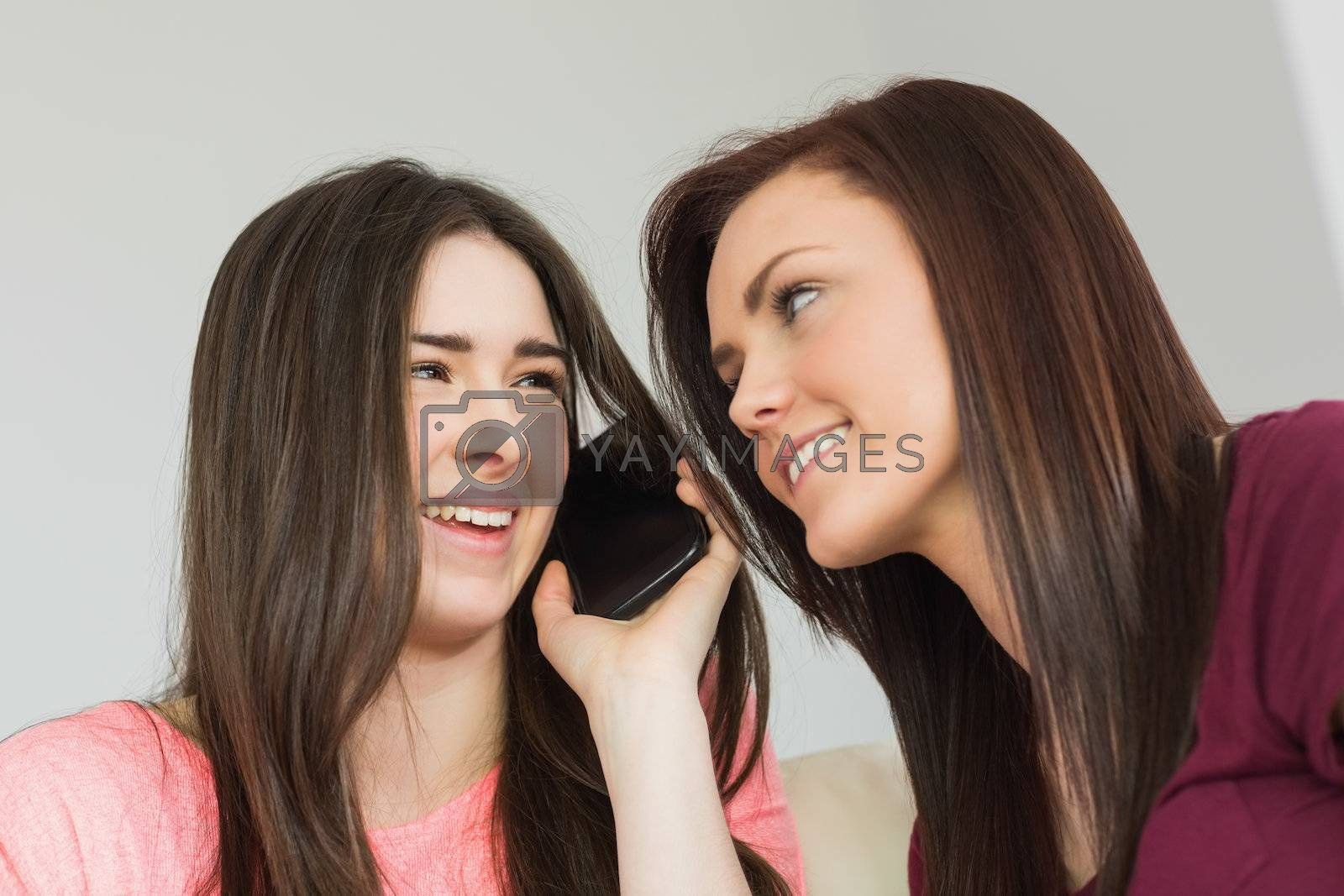 Two cheerful girls calling someone with a mobile phone by Wavebreakmedia