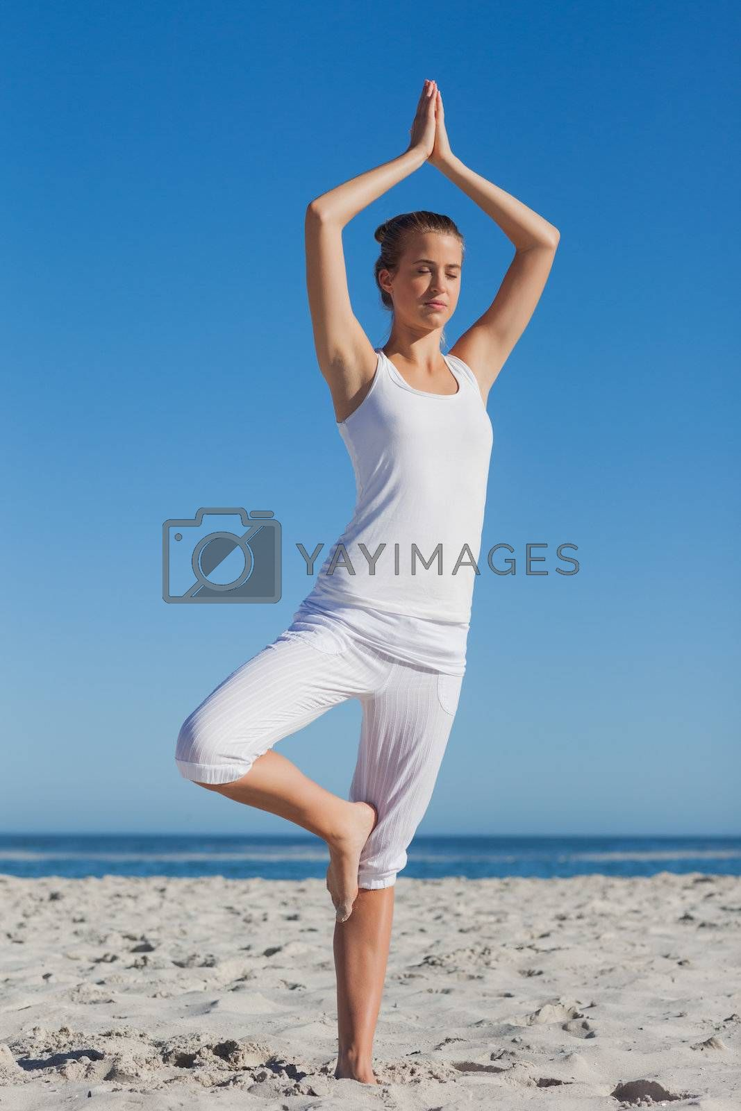 Woman in tree yoga pose by Wavebreakmedia