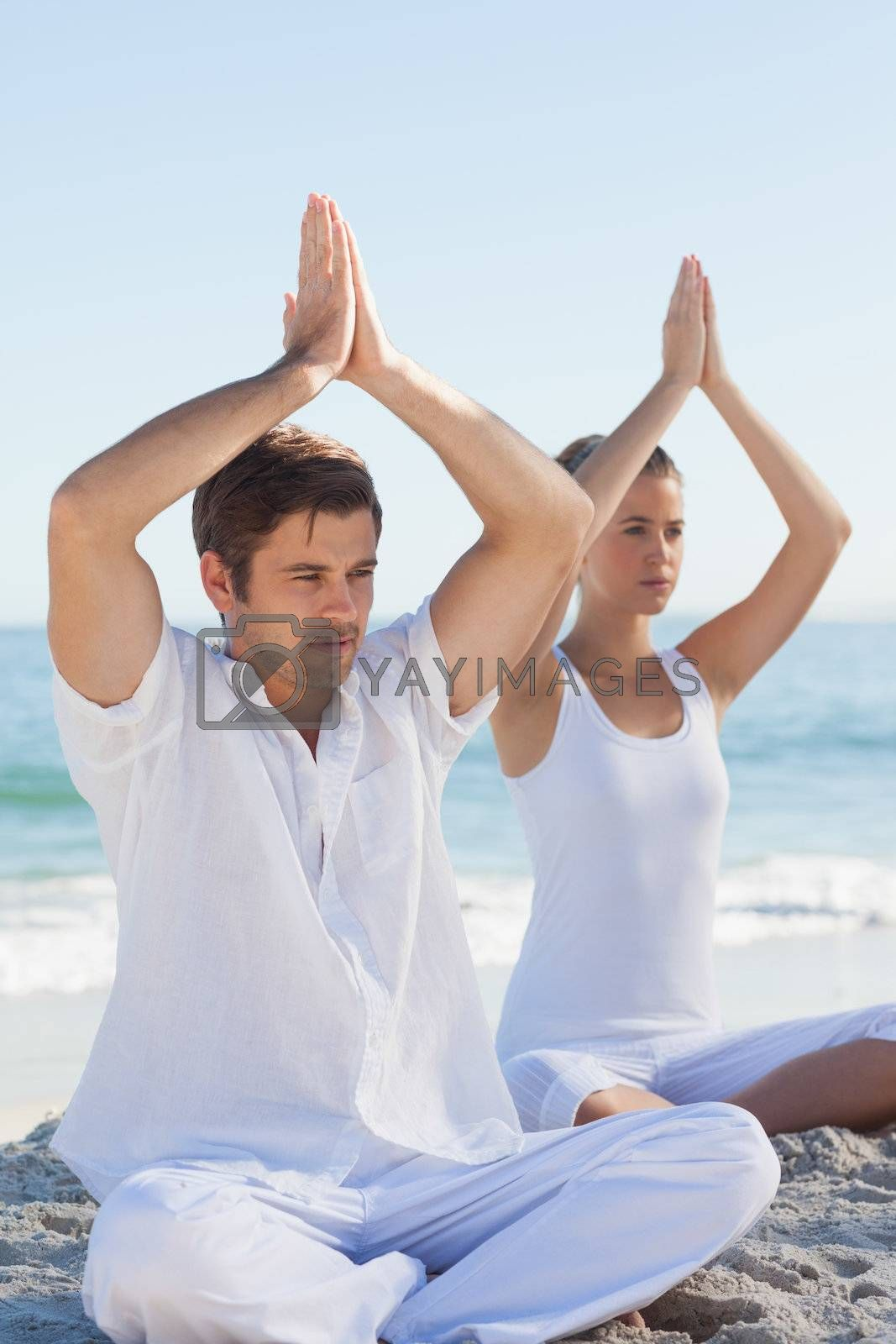 Concentrated woman and man practicing yoga by Wavebreakmedia