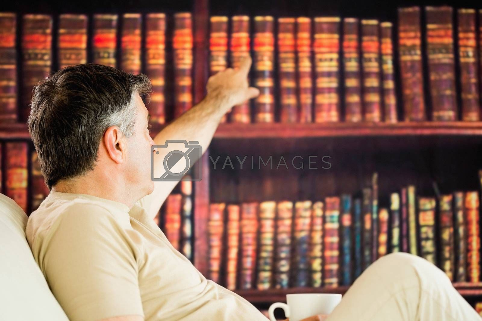 Sitting man picking a book in a reading room and drinkig coffee by Wavebreakmedia