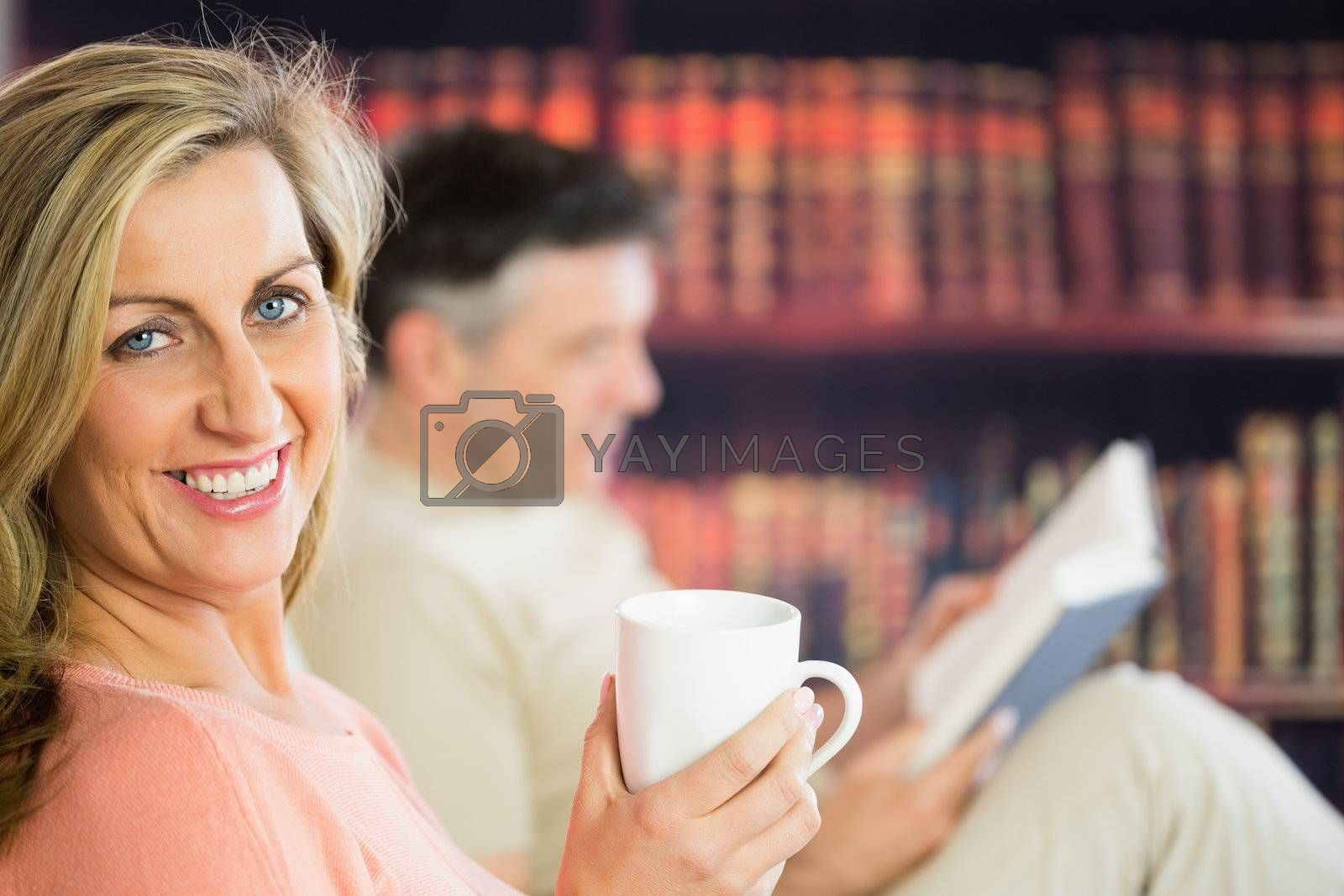 Happy couple reading and drinking coffee in a reading room by Wavebreakmedia