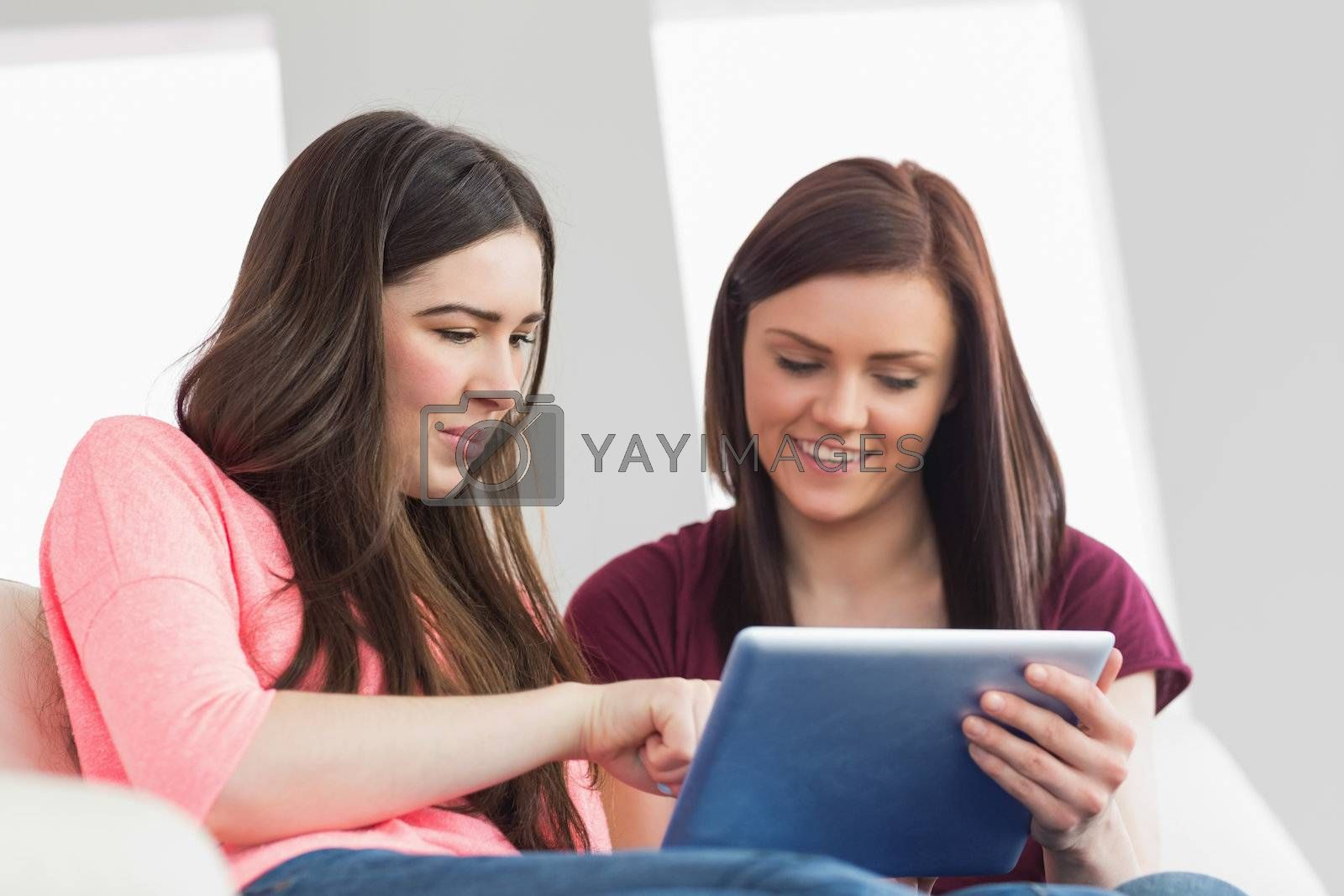 Two happy girls sitting on a sofa using a tablet pc by Wavebreakmedia