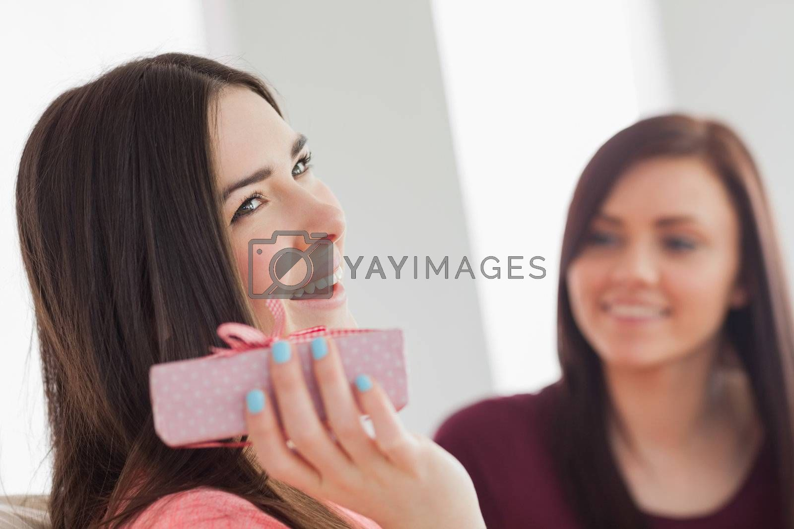 Smiling girl holding a present  by Wavebreakmedia