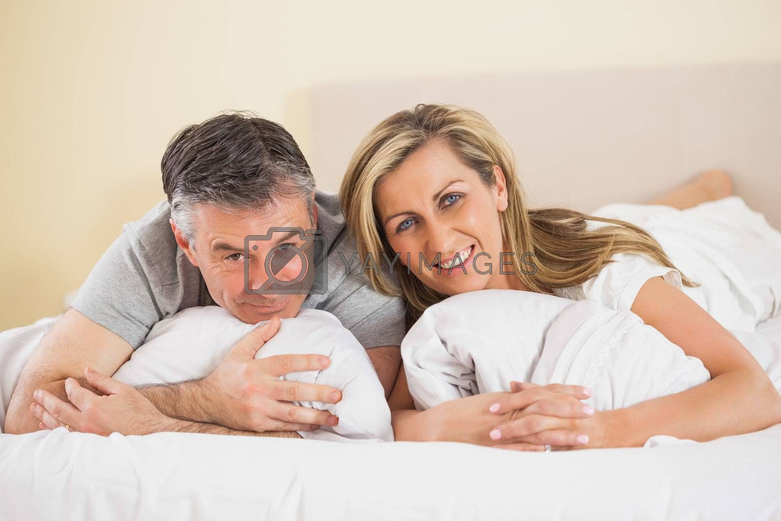 Happy couple lying on a bed and looking at camera by Wavebreakmedia