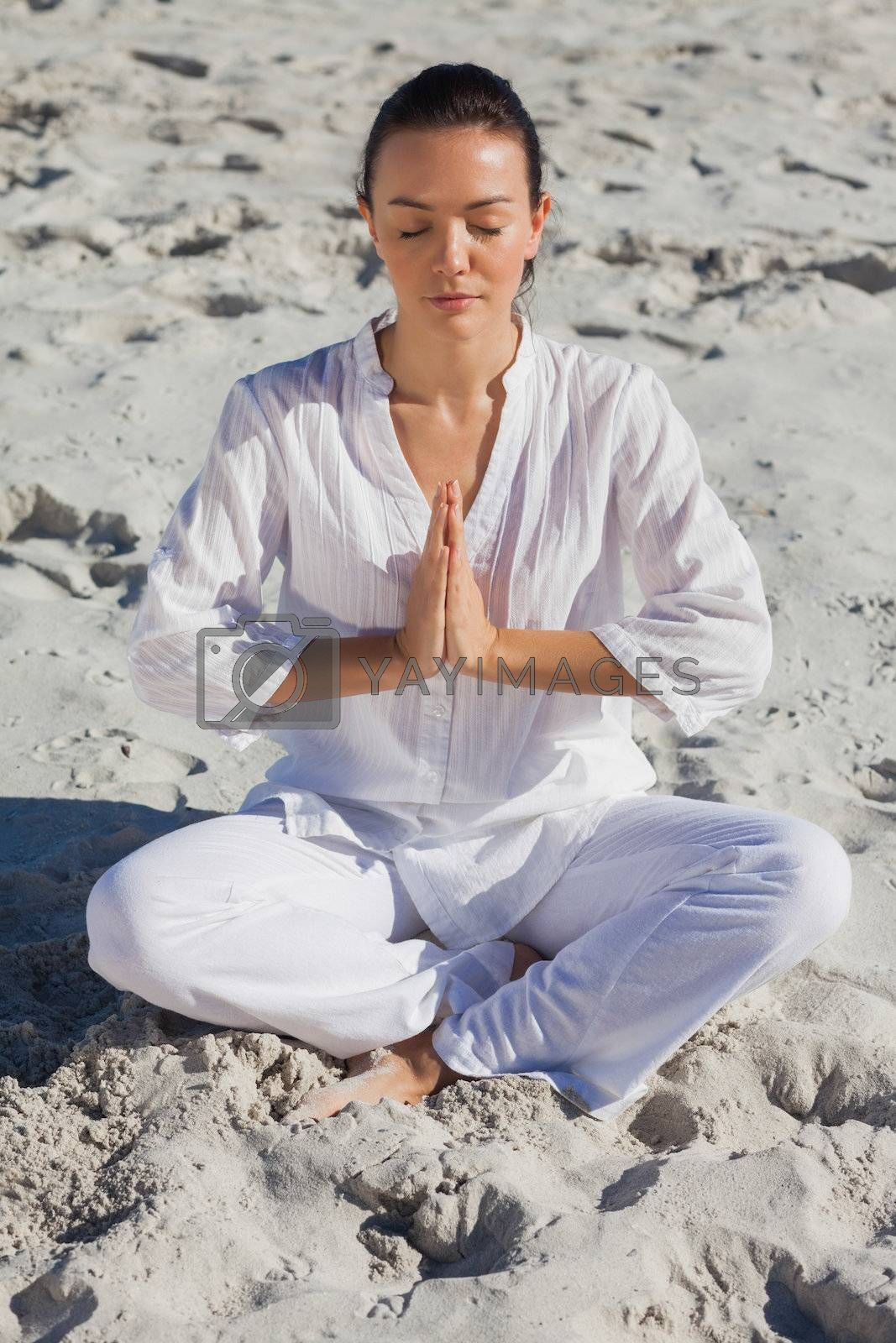 Concentrated woman practicing yoga on the beach  by Wavebreakmedia