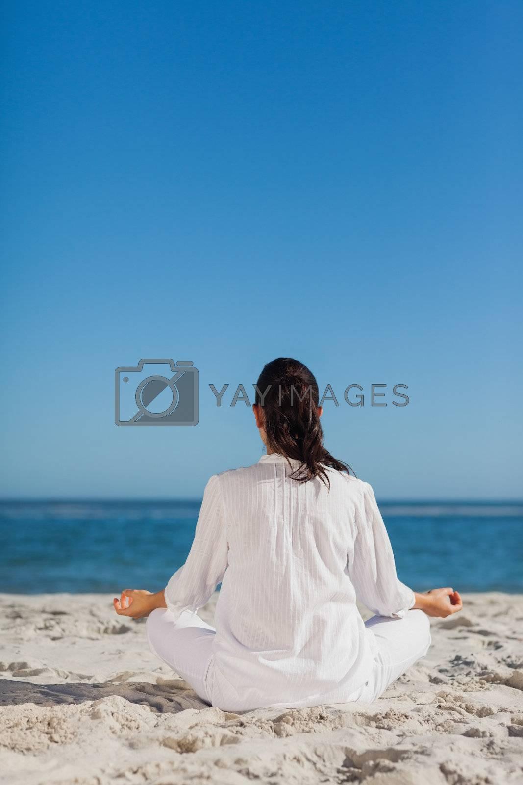 Woman sitting back to camera doing yoga by Wavebreakmedia