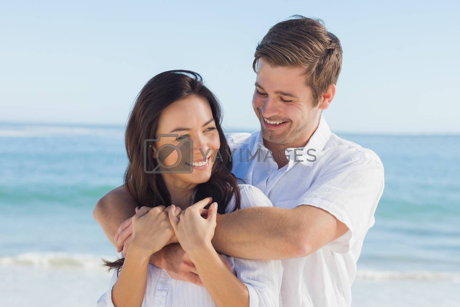 Cheerful couple relaxing on the beach during summer by Wavebreakmedia