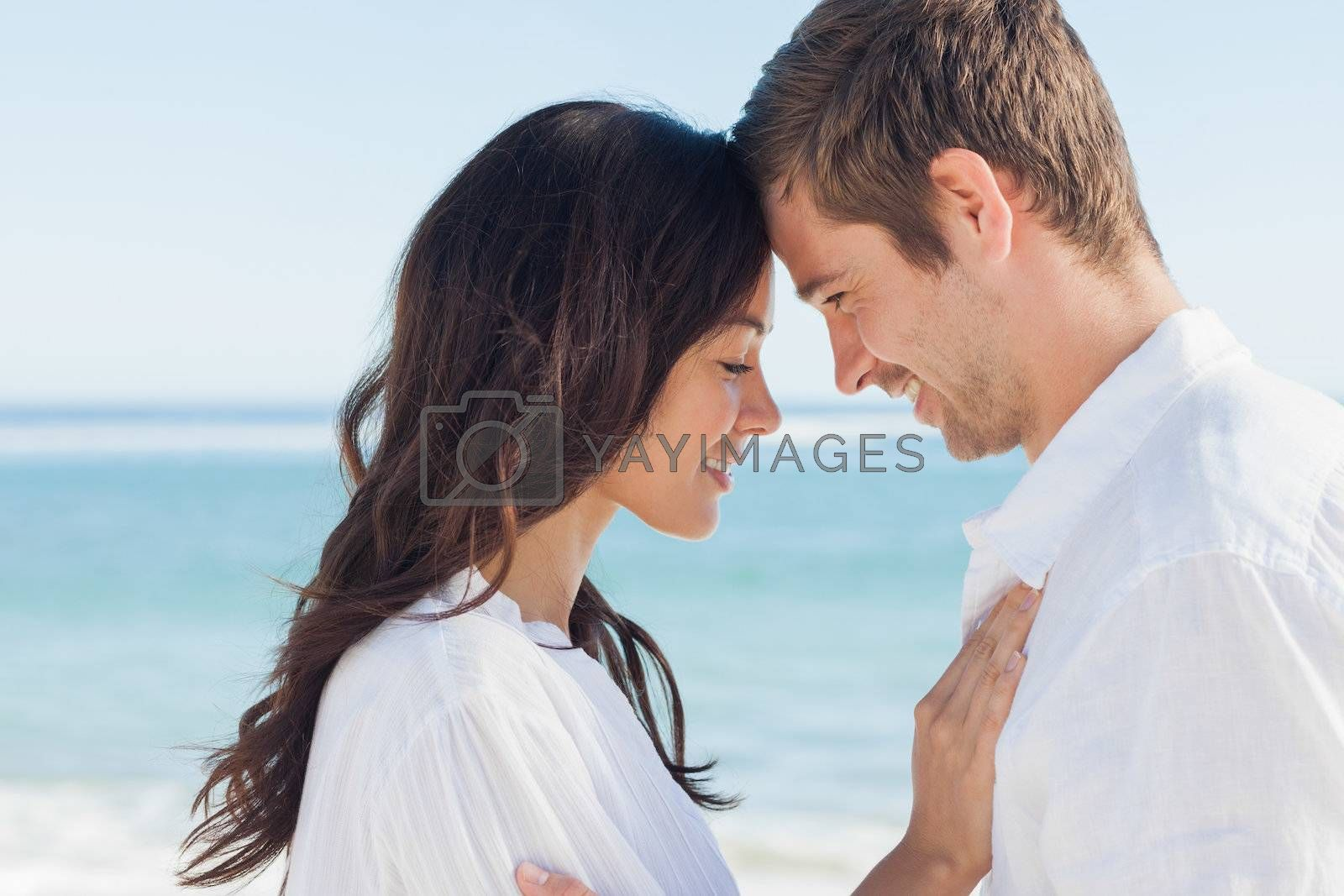 Romantic couple relaxing and embracing on the beach  by Wavebreakmedia