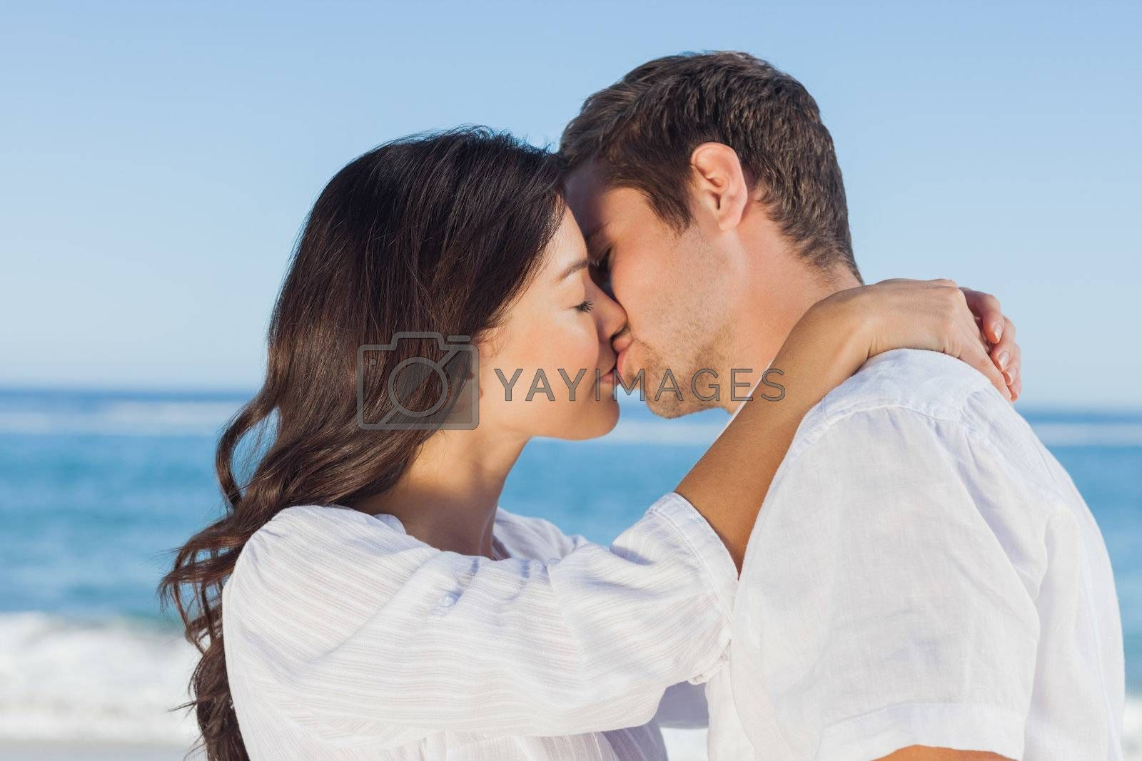 Couple embracing and kissing each other on the beach by Wavebreakmedia