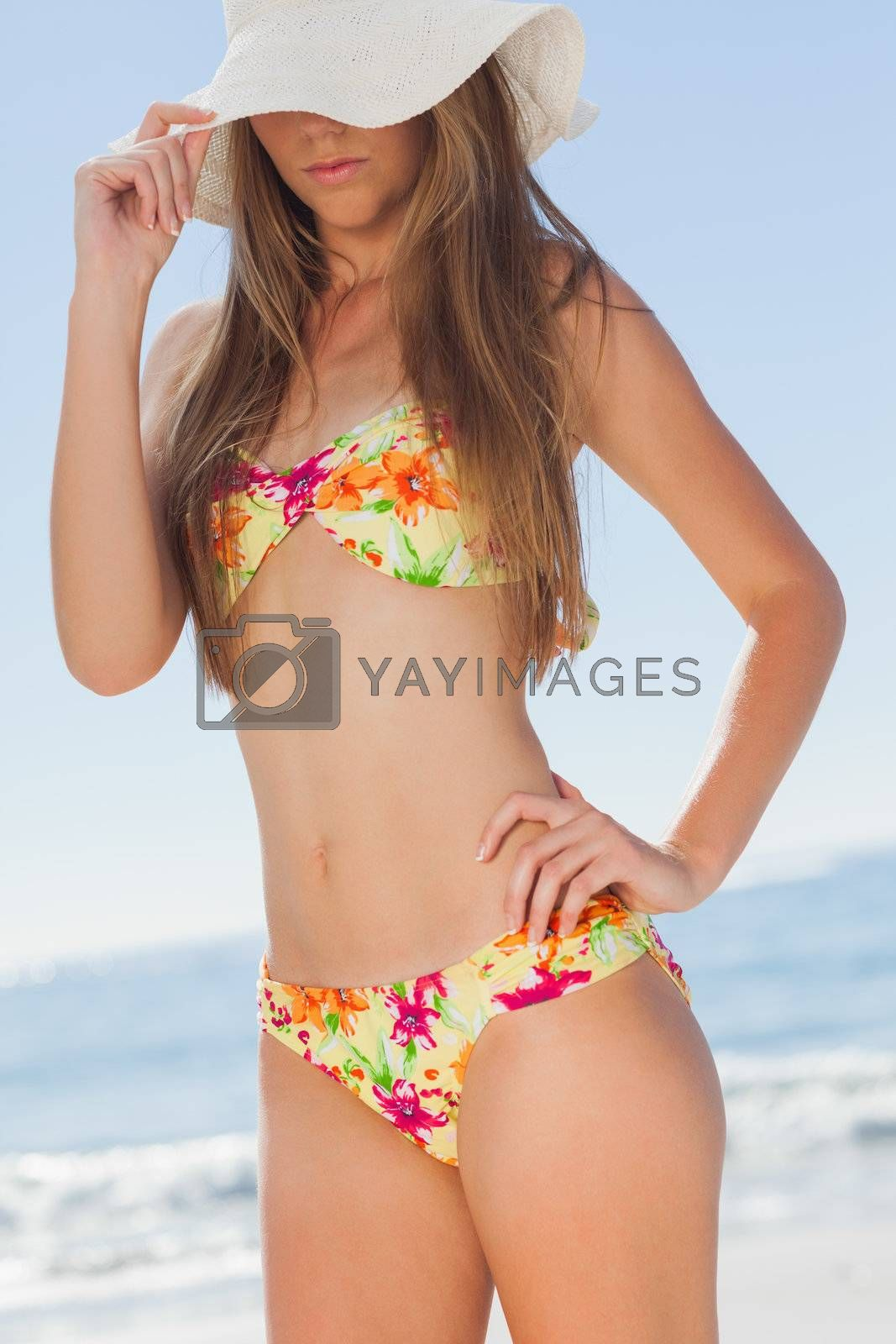 Young attractive woman standing on the beach by Wavebreakmedia