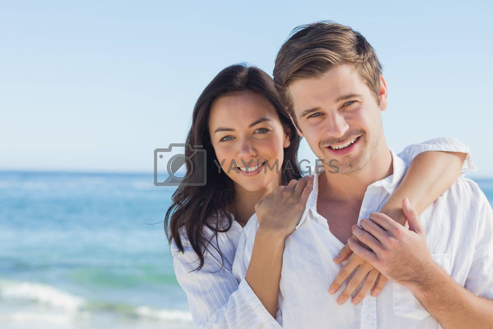 Cheerful couple embracing on the beach  by Wavebreakmedia