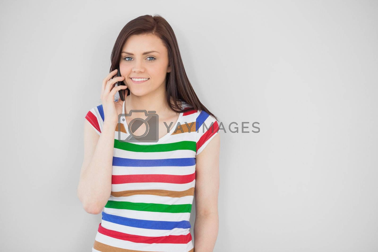 Smiling girl calling with her mobile phone looking at camera by Wavebreakmedia