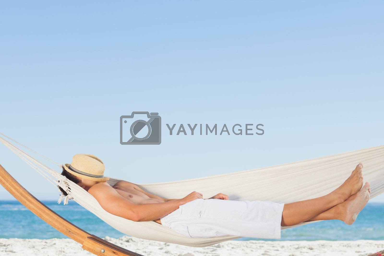 Man wearing straw hat relaxing in a hammock  by Wavebreakmedia