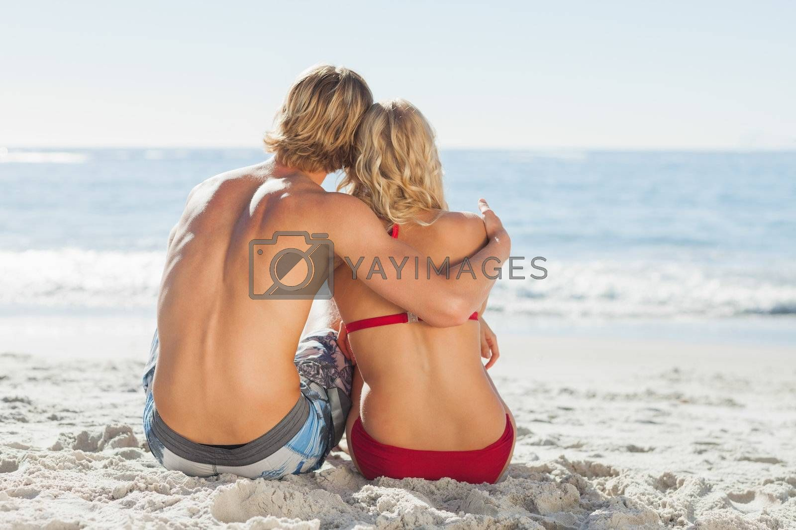 Rear view of a young couple sitting on the beach in front of the sea