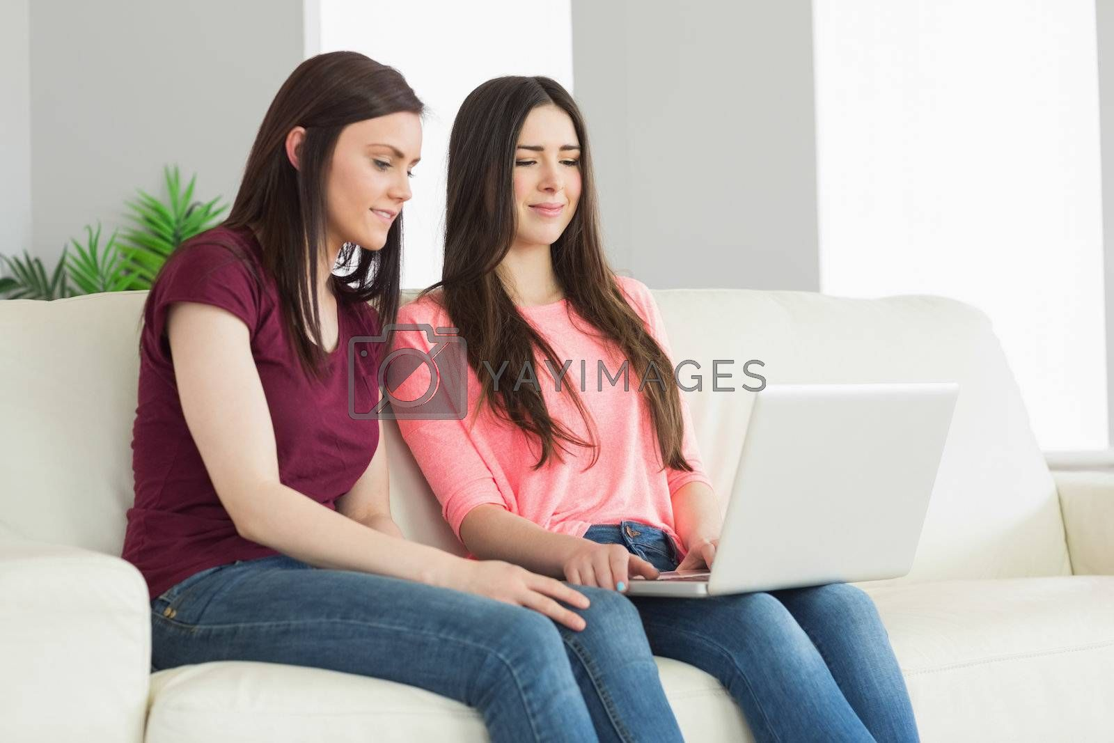 Two teenagers sitting on a sofa and watching a laptop by Wavebreakmedia