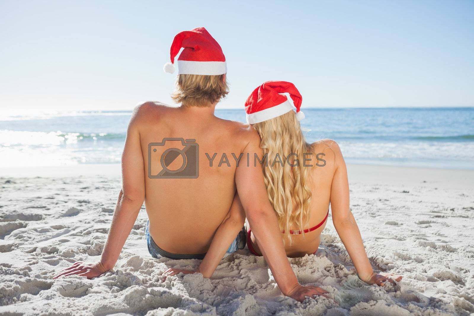 Rear view of couple sitting on beach  by Wavebreakmedia